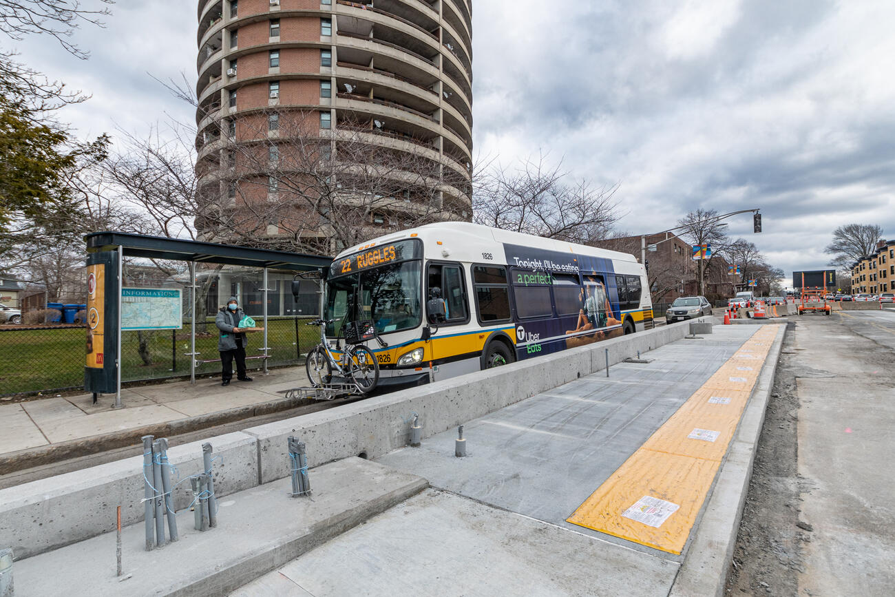A Route 22 bus outbound to Ruggles passes by a new concrete bus boarding platform under construction near the intersection of Columbus Ave and Weld Ave. The concrete boarding platform is separate from the sidewalk, located between one traffic lane and a future bus lane under construction, and is approximately 9 inches tall relative to the surface of the road and 9 feet wide. The concrete foundation is mostly complete, however, amenities are not yet installed.