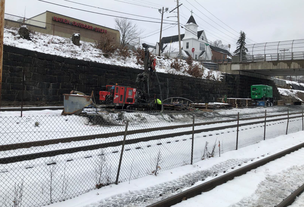 The outbound Natick track west of Washinton Bridge, shown covered in snow. Various construction equipment and materials are shown lined up on the side.