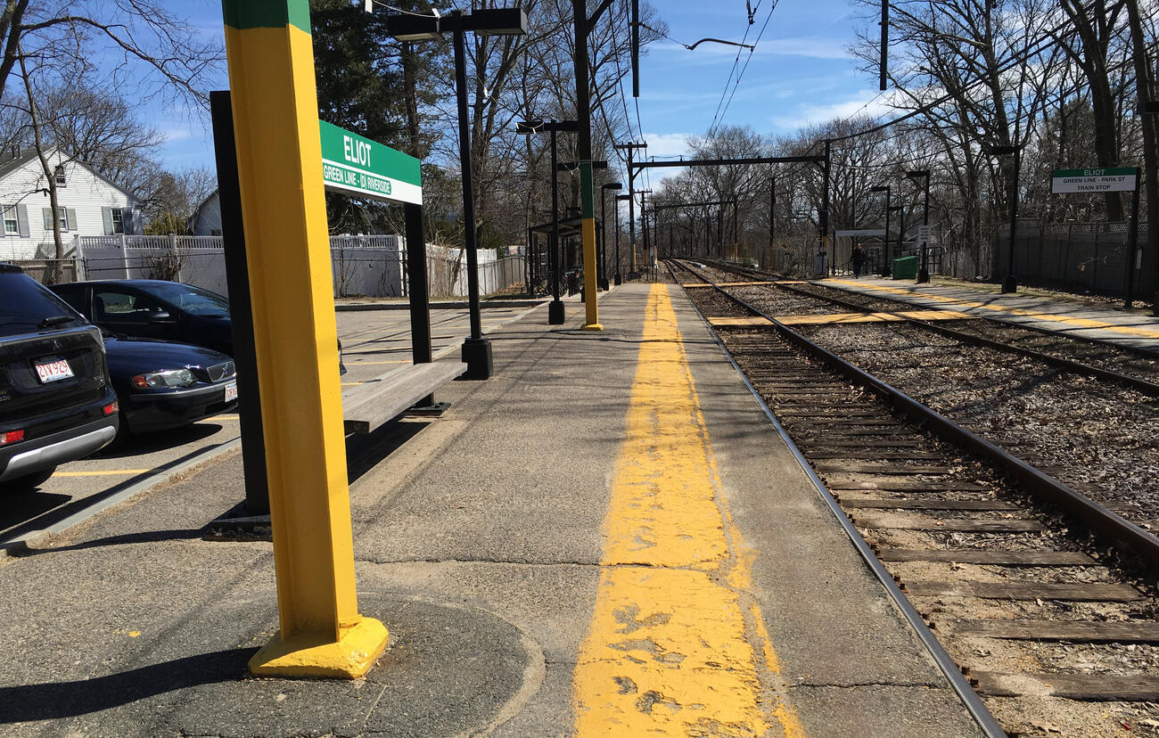 The Eliot station platform. Concrete is uneven and there are many large poles in the walkway