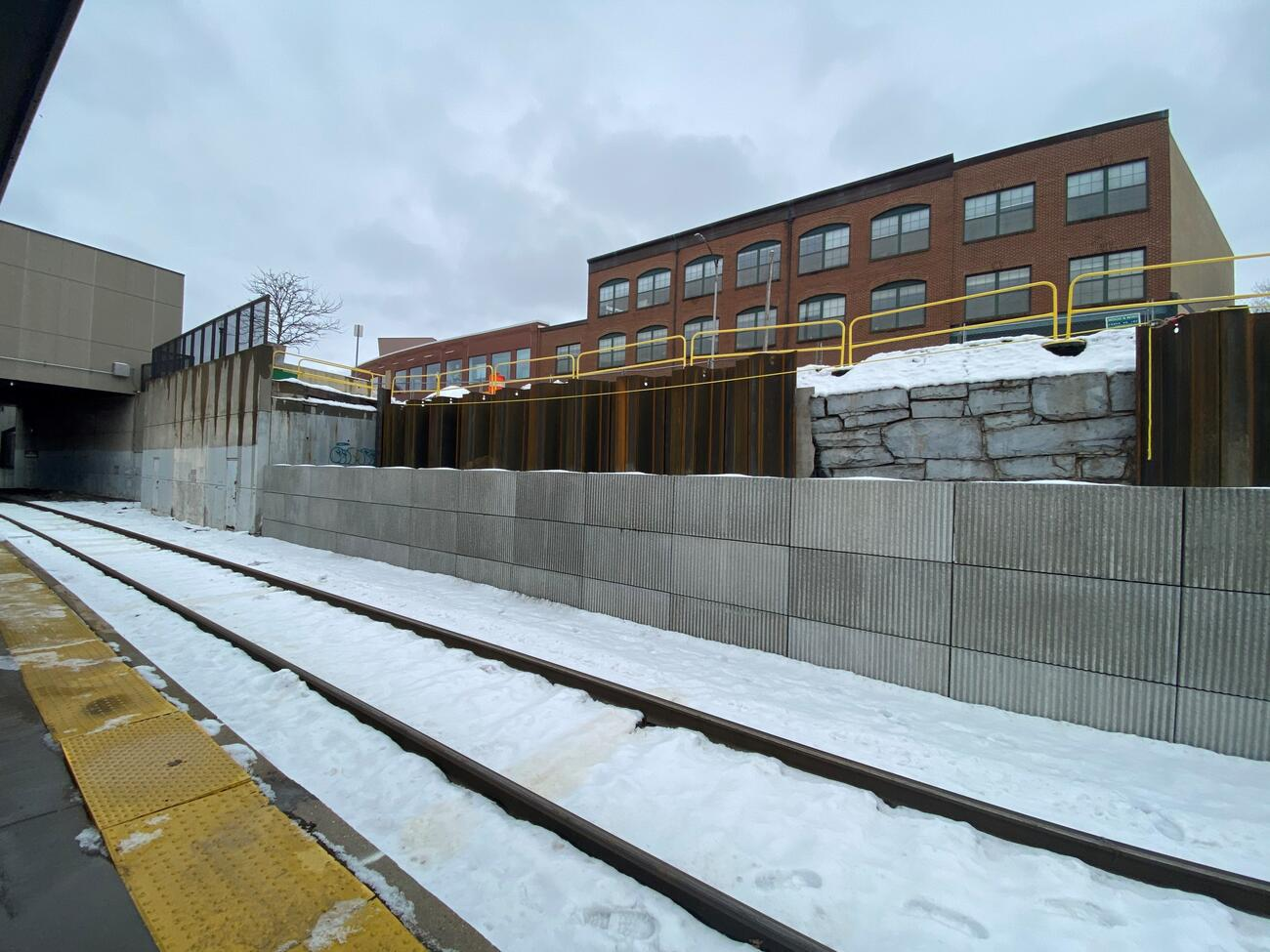 A view of the t-wall construction from the station platform. It's a gray day and the tracks are covered in snow