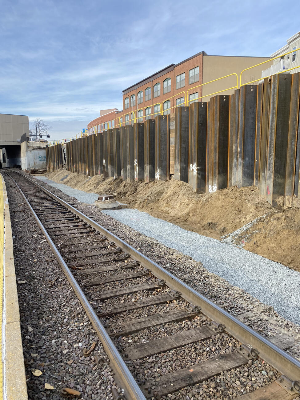 A picture of the construction work taken from the station platform. The tracks are in the foreground and large, tall metal sheets have been installed next to the wall to stabilize it.