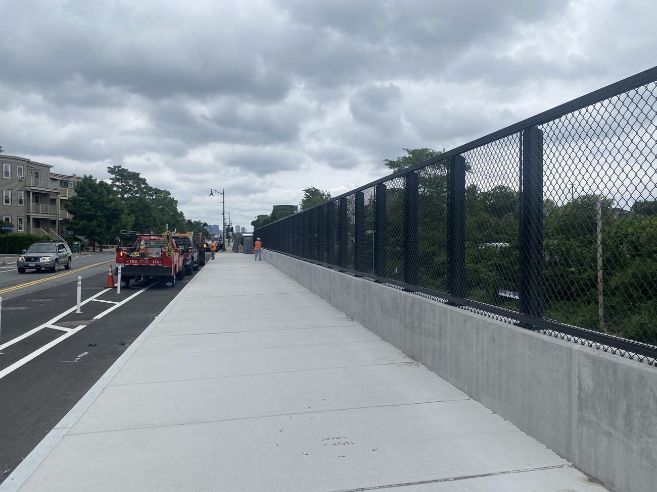 Completed sidewalk, barrier, and fence atPorter Square (June 2021)