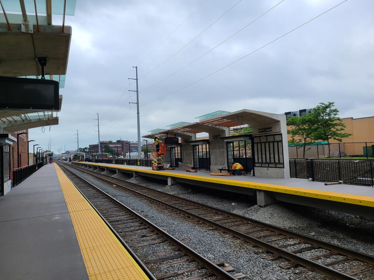 Crews install benches and wire lighting for the new Chelsea Commuter Rail Station outbound platform.