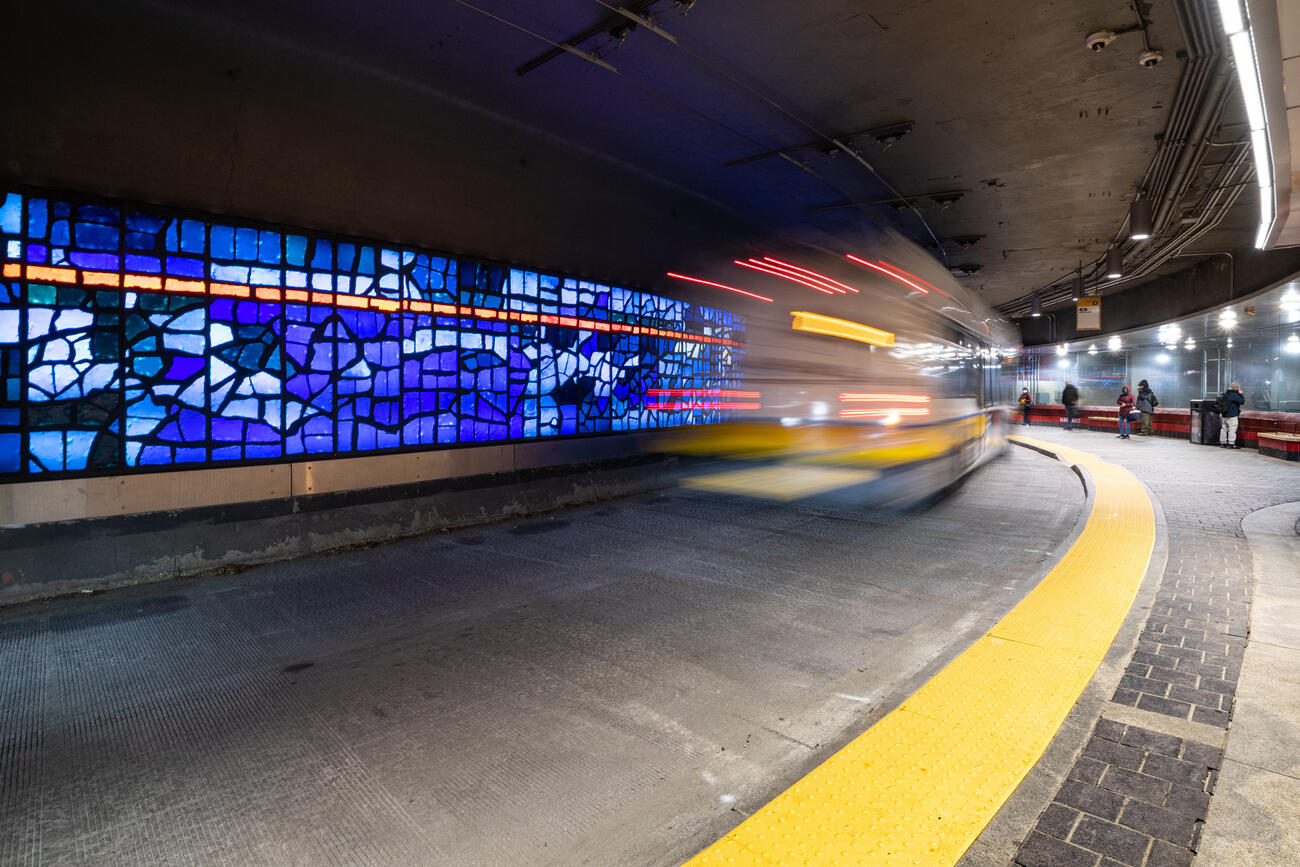 """A bus passes György Kepes' stained-glass installation """"Blue Sky on the Red Line"""" on the Upper Busway at Harvard Station (February 2021)."""