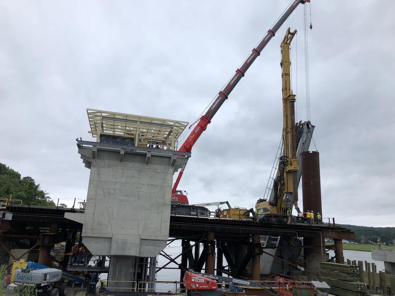 The control tower under construction is in the foreground. Behind it on the bridge are construction cranes, one of which is suspending one of the two northern drilled shafts vertically is it is being moved into place. Several workers in bright construction gear stand on the bridge and guide the placement of the shaft.