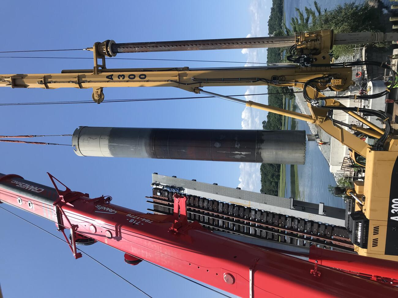 In the foreground, red and yellow cranes suspend one of the northern shafts during installation. In the background, a worker stands on the bridge facing the shaft as it hangs in midair, all against a backdrop of water, tree-covered shoreline, and blue sky.