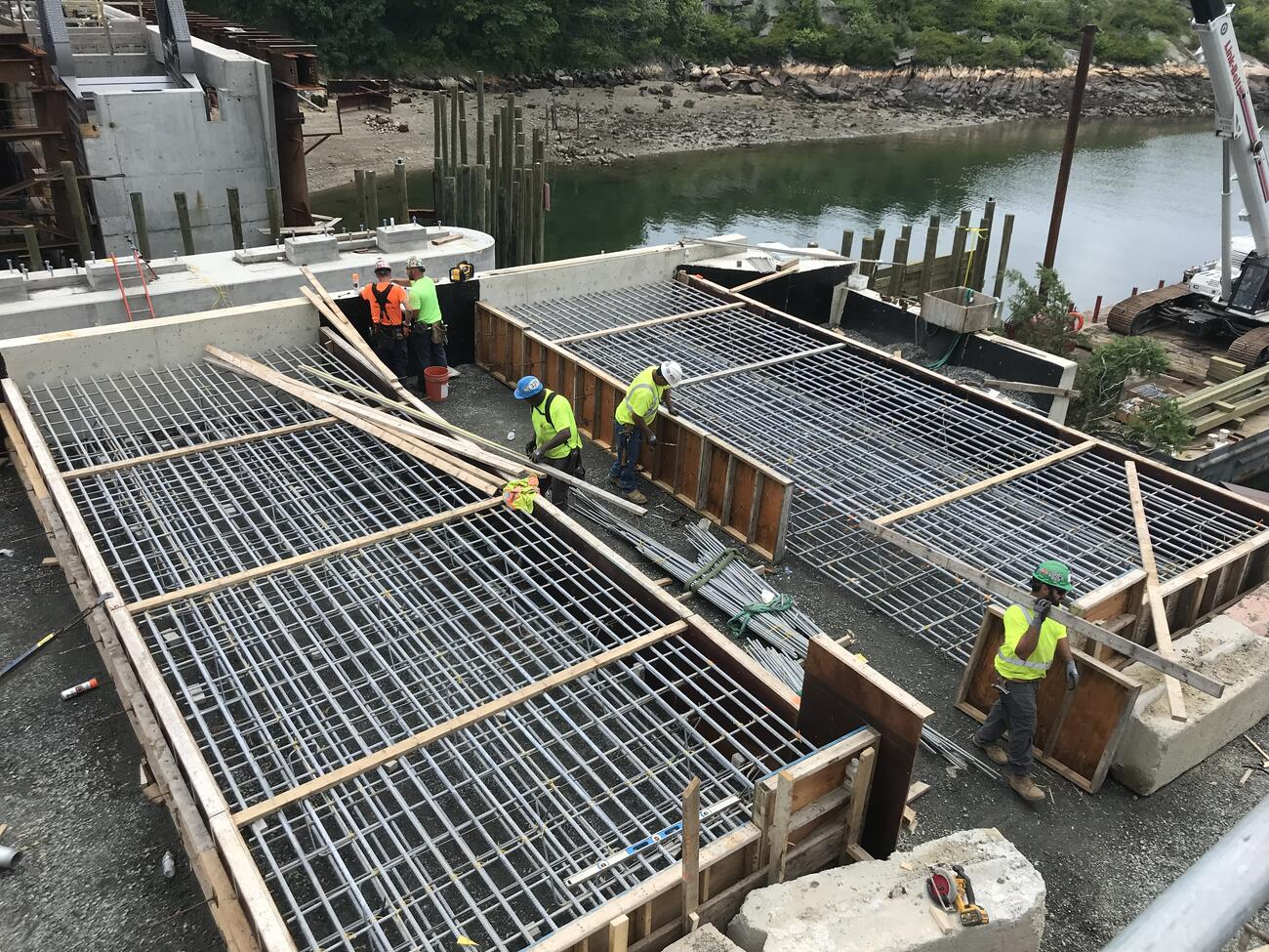 Five workers build large wooden forms crisscrossed with metal reinforcing bars before the forms are filled with concrete to create the approach slabs leading to the bridge. Wooden piers and the waterway are visible in the background.