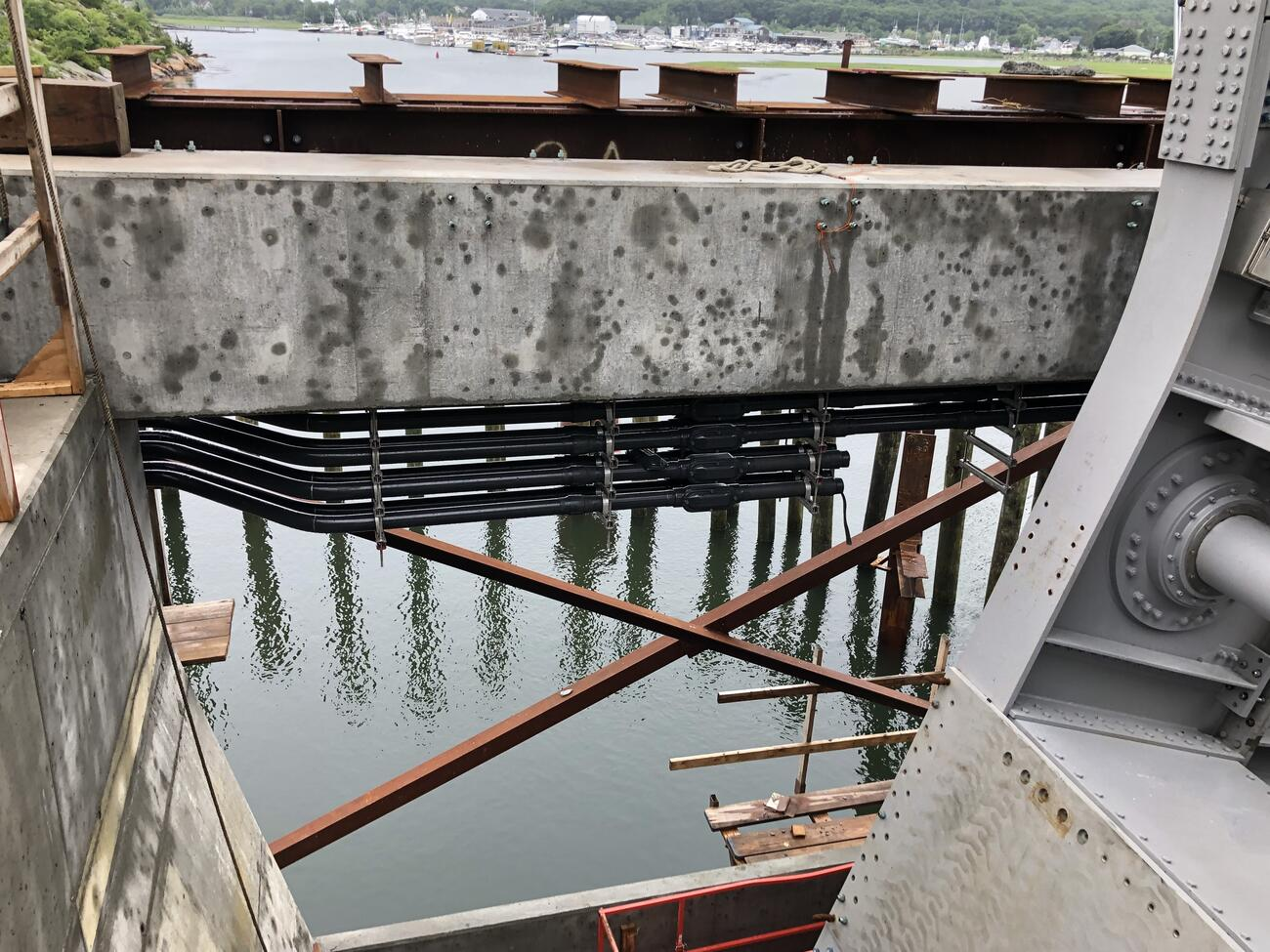 At top, I-beams rest perpendicular to a riveted steel beam that spans the image horizontally. Below that is a large horizontal cement structure, suspended from which are long, black, horizontal conduit pipes. The center of the image looks down onto the waterway, which is framed by a cement wall at left and riveted steel structural elements on the right.
