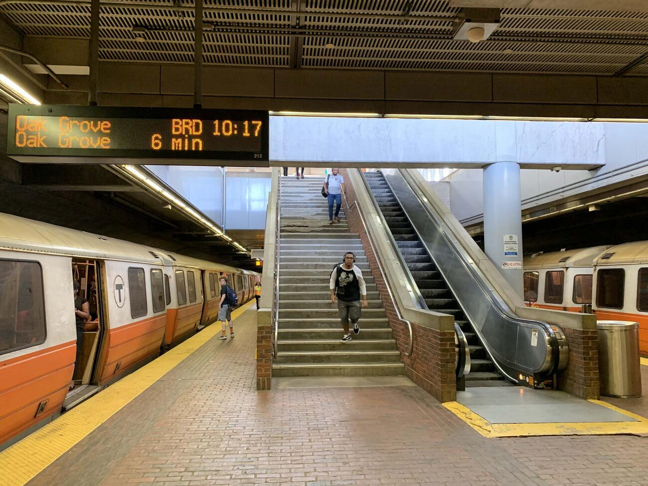 An orange line train waiting at the Forest Hills Station tracks