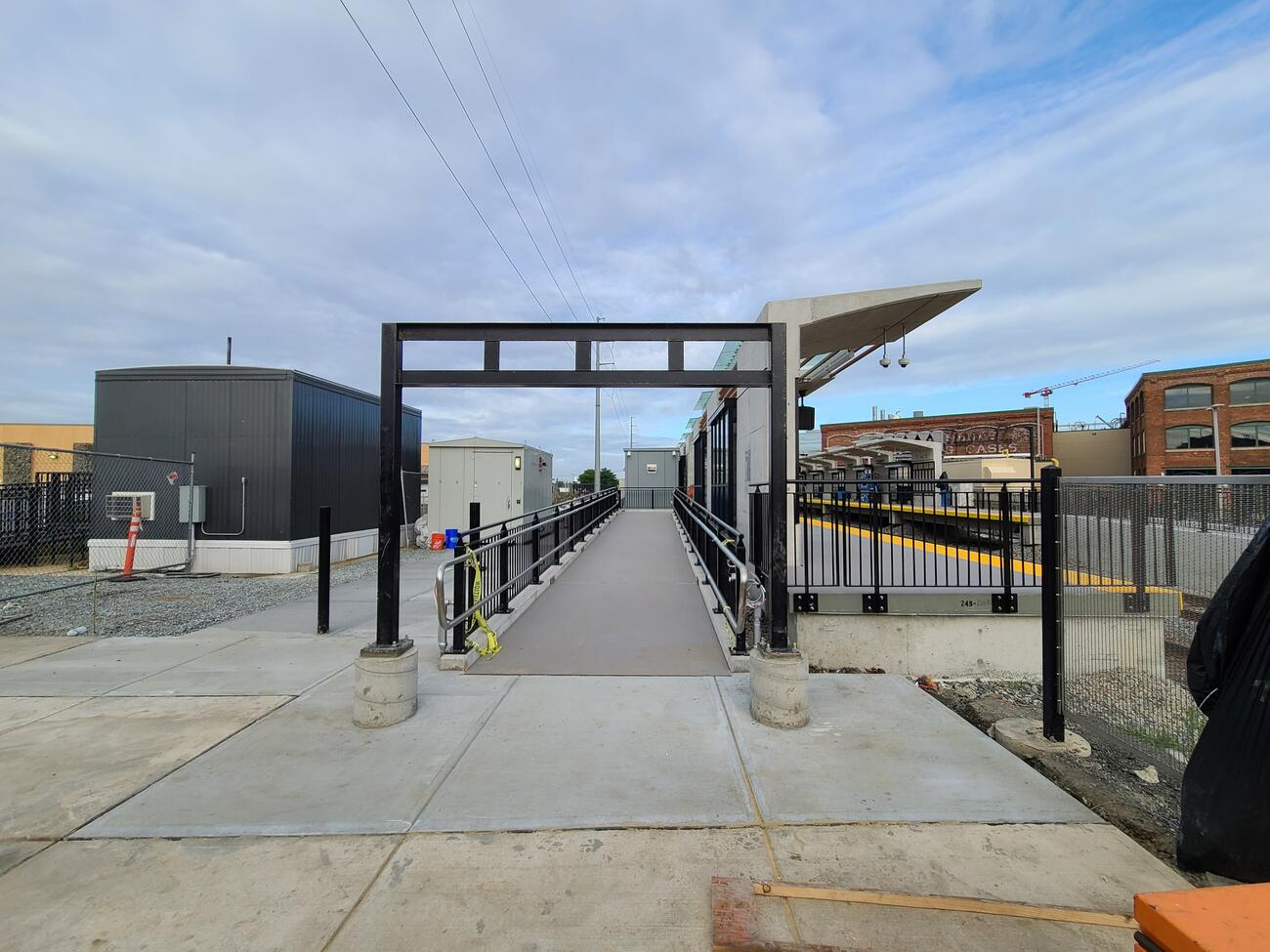 At center is a ramp leading from the Silver Line stop up to the outbound Commuter Rail station platform. The ramp is open to the sky, but has handrails on both sides.