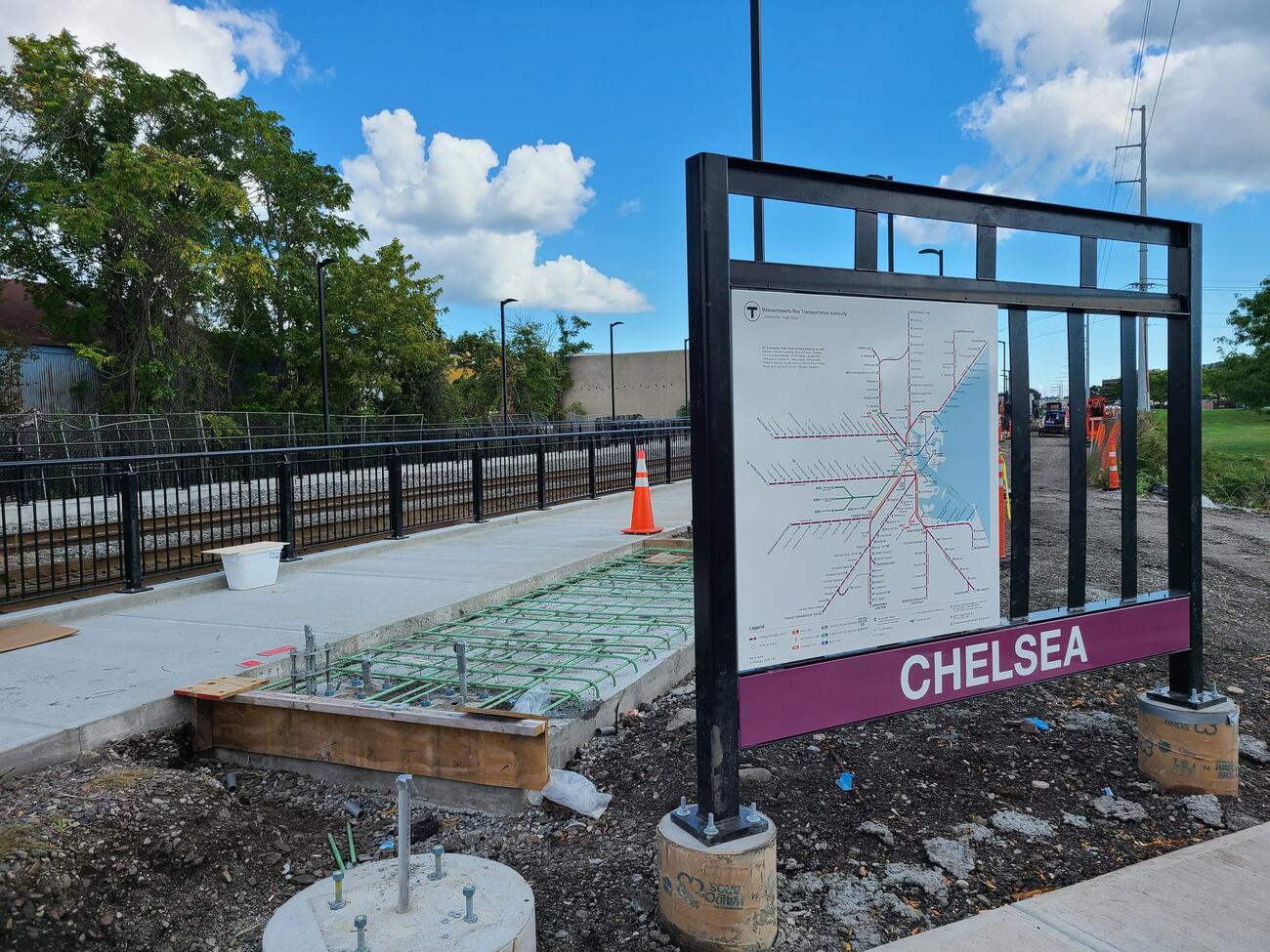 At right are the Chelsea station sign and map, partially installed. At left is a new sidewalk alongside a long rectangular foundation frame made of wood, cement and a grid of metal bars upon which bike racks will be built. A fence runs from the left edge to the center separating the sidewalk from the train tracks. A blue sky with white clouds can be seen above.
