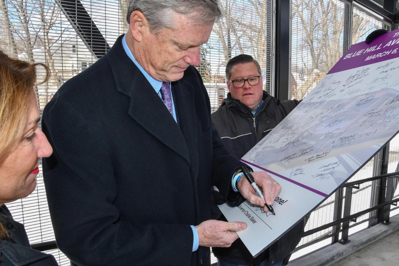Governor Charlie Baker signing a Blue Hill Ave sign