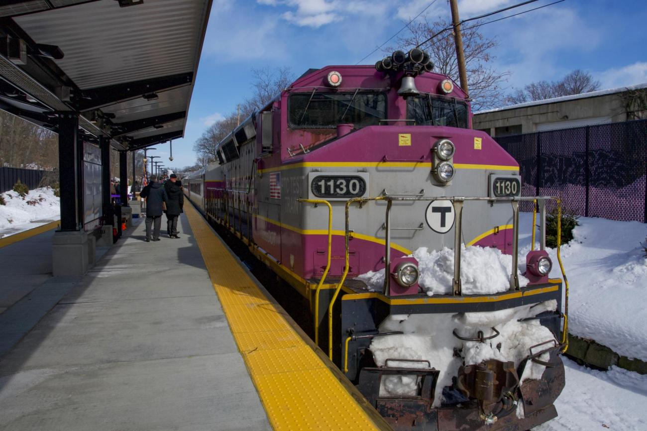 A Commuter Rail train with snow pulls up to the new station's platform.