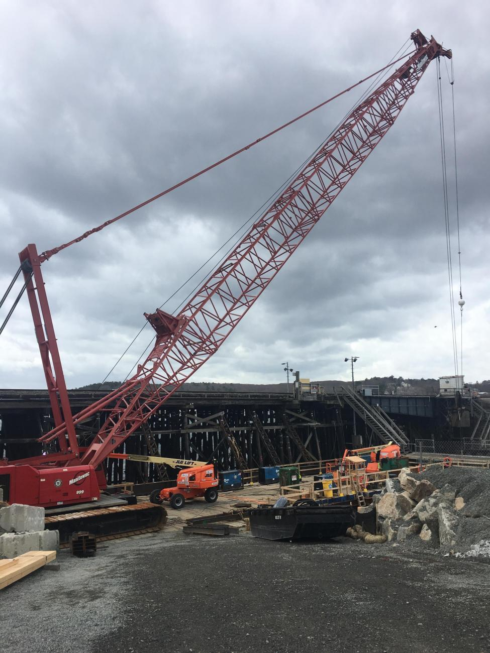 Ground level view of a large red crane at the Gloucester Drawbridge construction site.