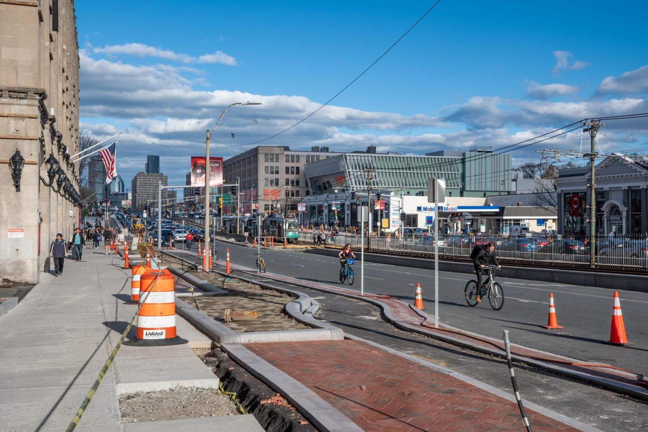 Construction on Commonwealth Ave during spring 2019, showing a new bike lane with a buffer from the traffic lanes.