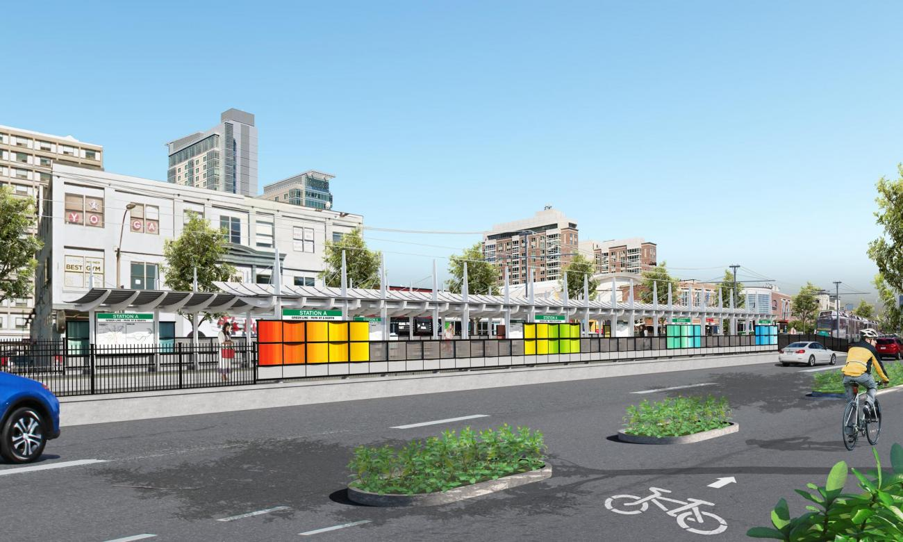 Rendering of the proposed station between Harry Agganis Way and Babcock St, viewed from the sidewalk, with traffic lanes and a bicycle lane in the foreground.