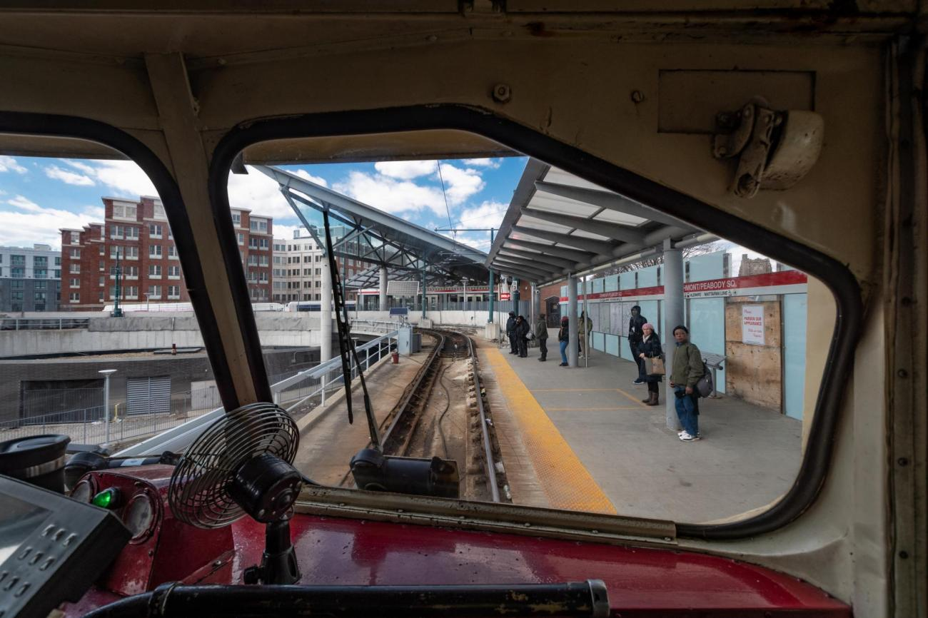 A view through the front windows of a Mattapan Line trolley as it approaches Ashmont Station, where riders are waiting on the platform