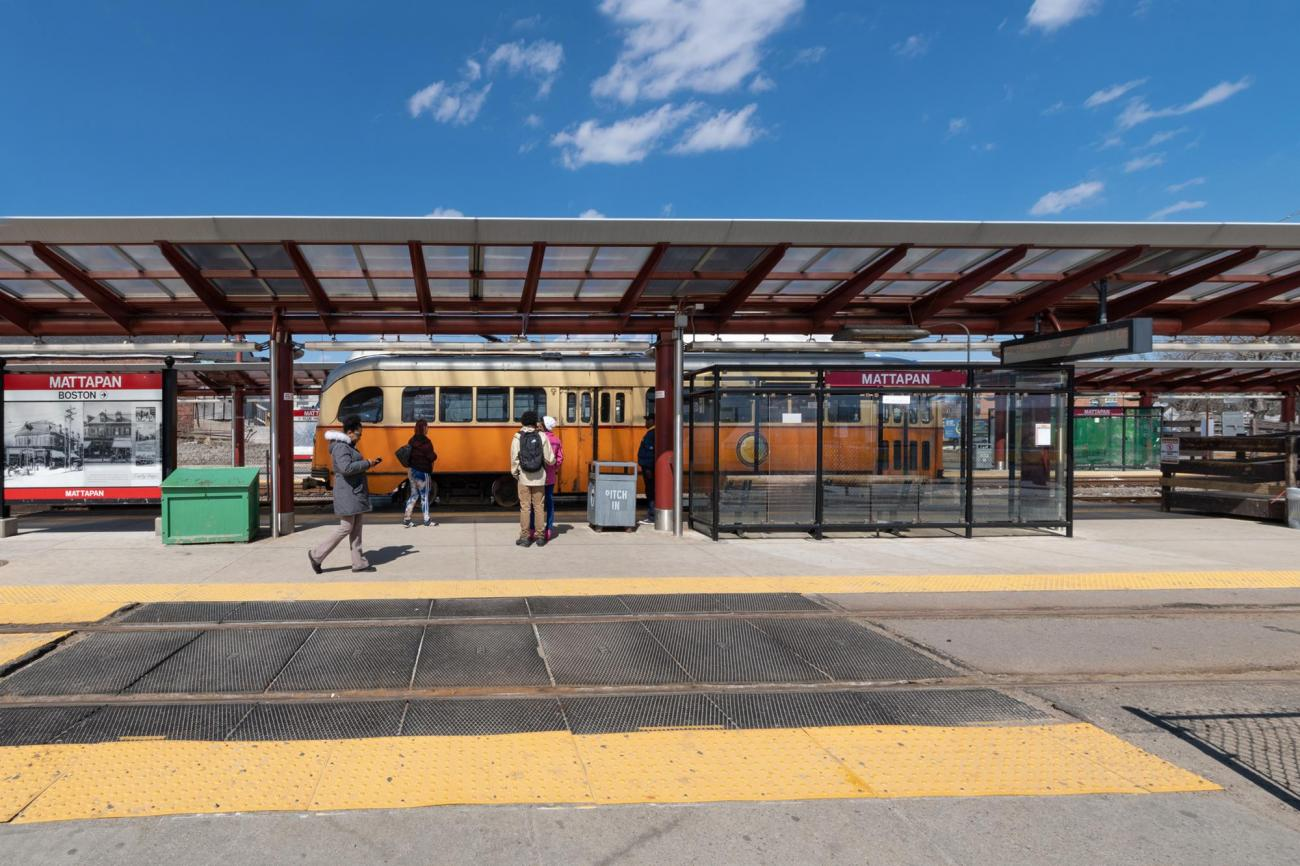 A trolley pulls up to Mattapan Station, with riders ready to board
