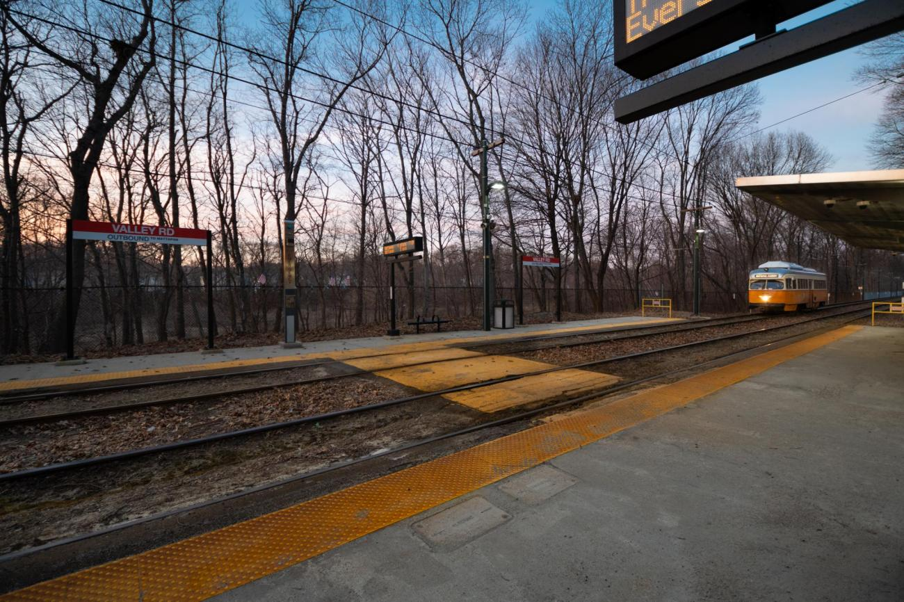 At dusk, a Mattapan Line trolley approaches Valley Road Station