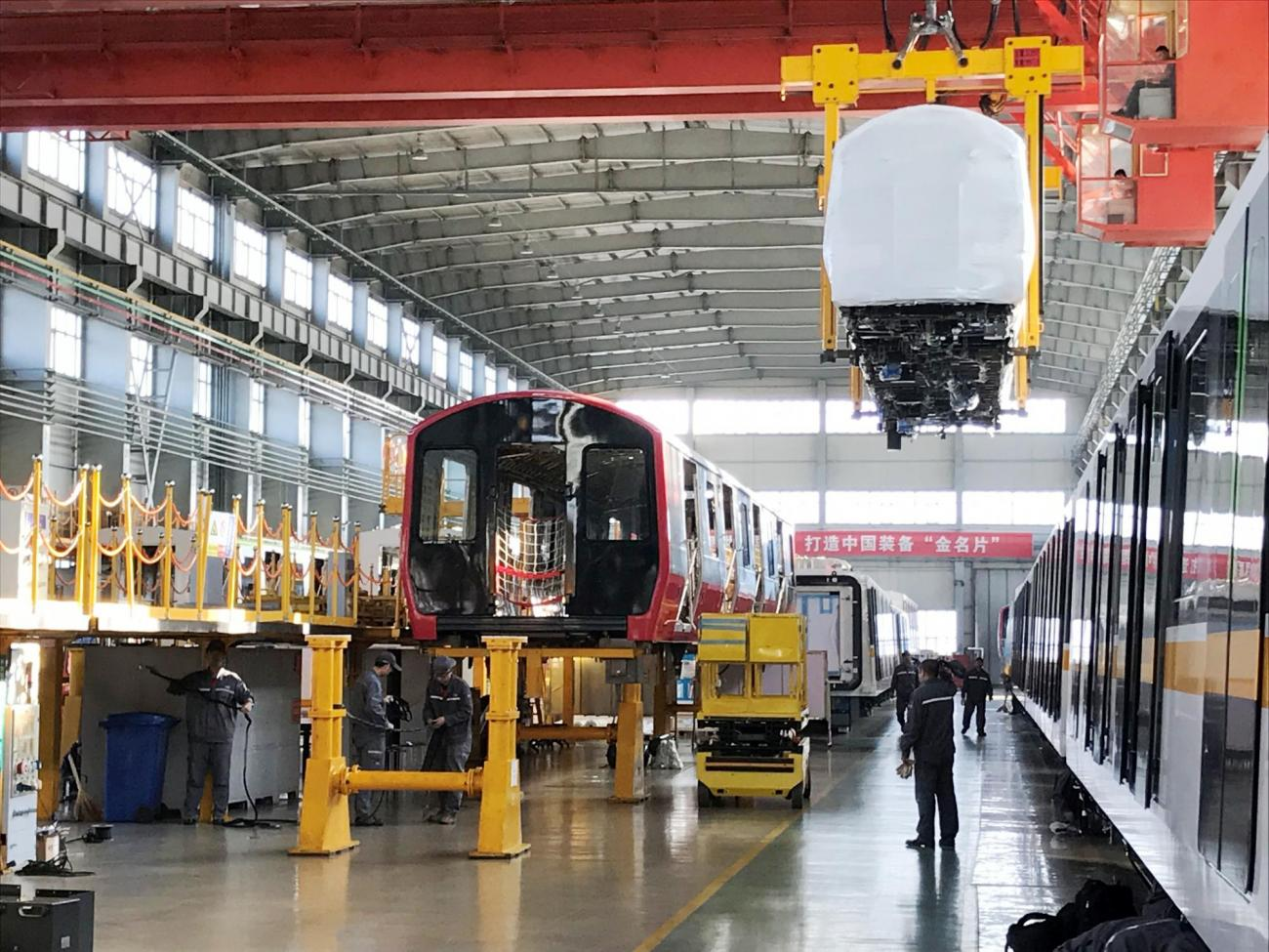 Red Line pilot car being outfitted, while a wrapped Orange Line production shell is being loaded for shipment from in Changchun, China to Springfield, MA