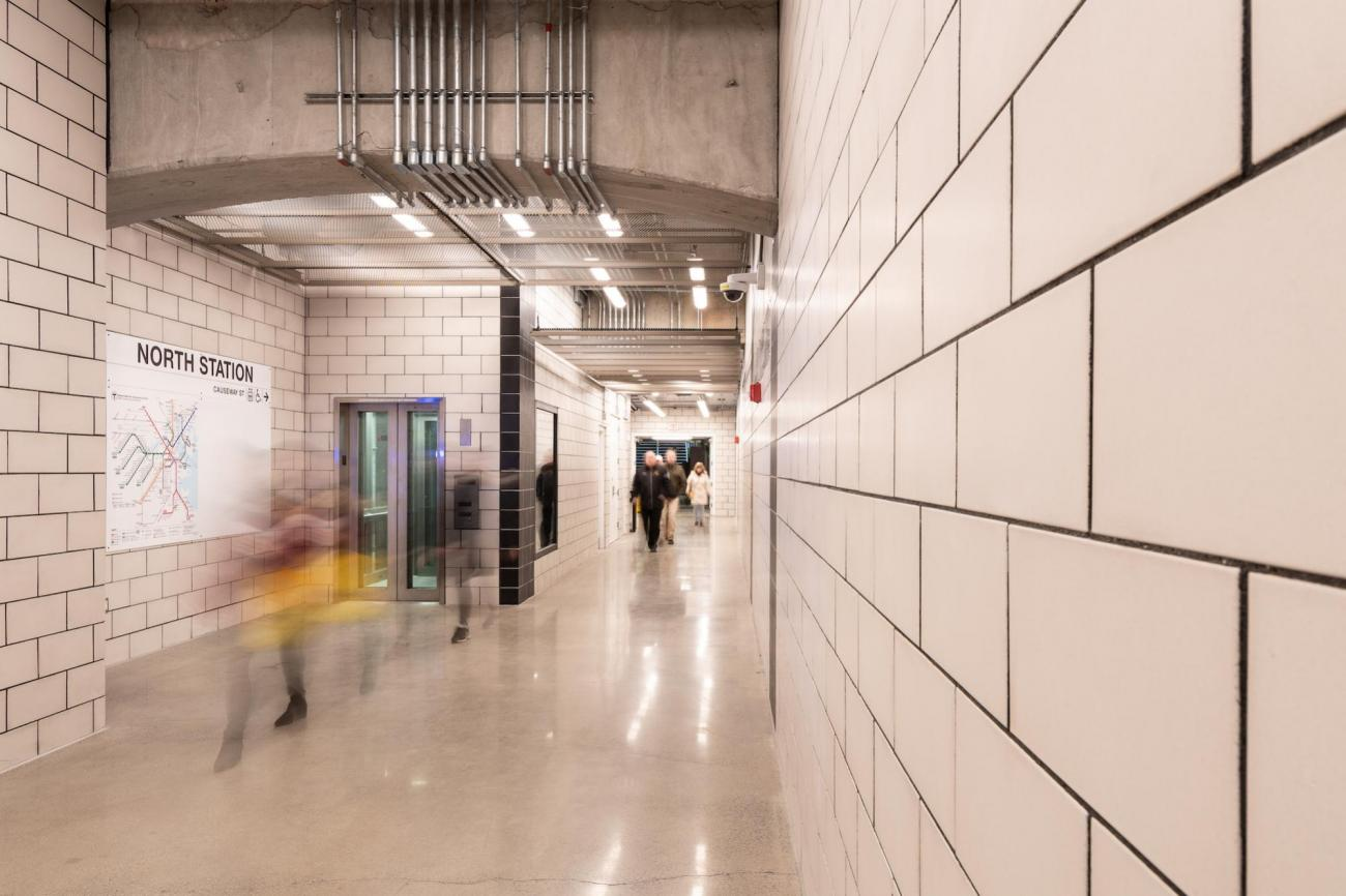North Station underground walkway, with people traversing and an MBTA system map