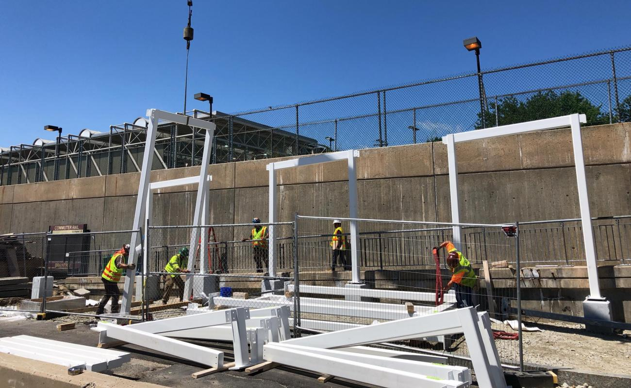 A crew erects columns and beams for a canopy over the pedestrian ramp to the Commuter Rail platform at Braintree Station.
