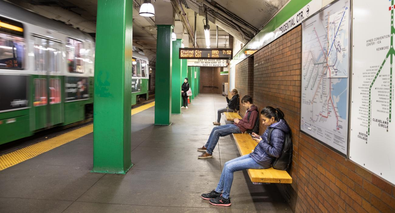 Riders wait for the Green Line at Hynes, checking their smartphones