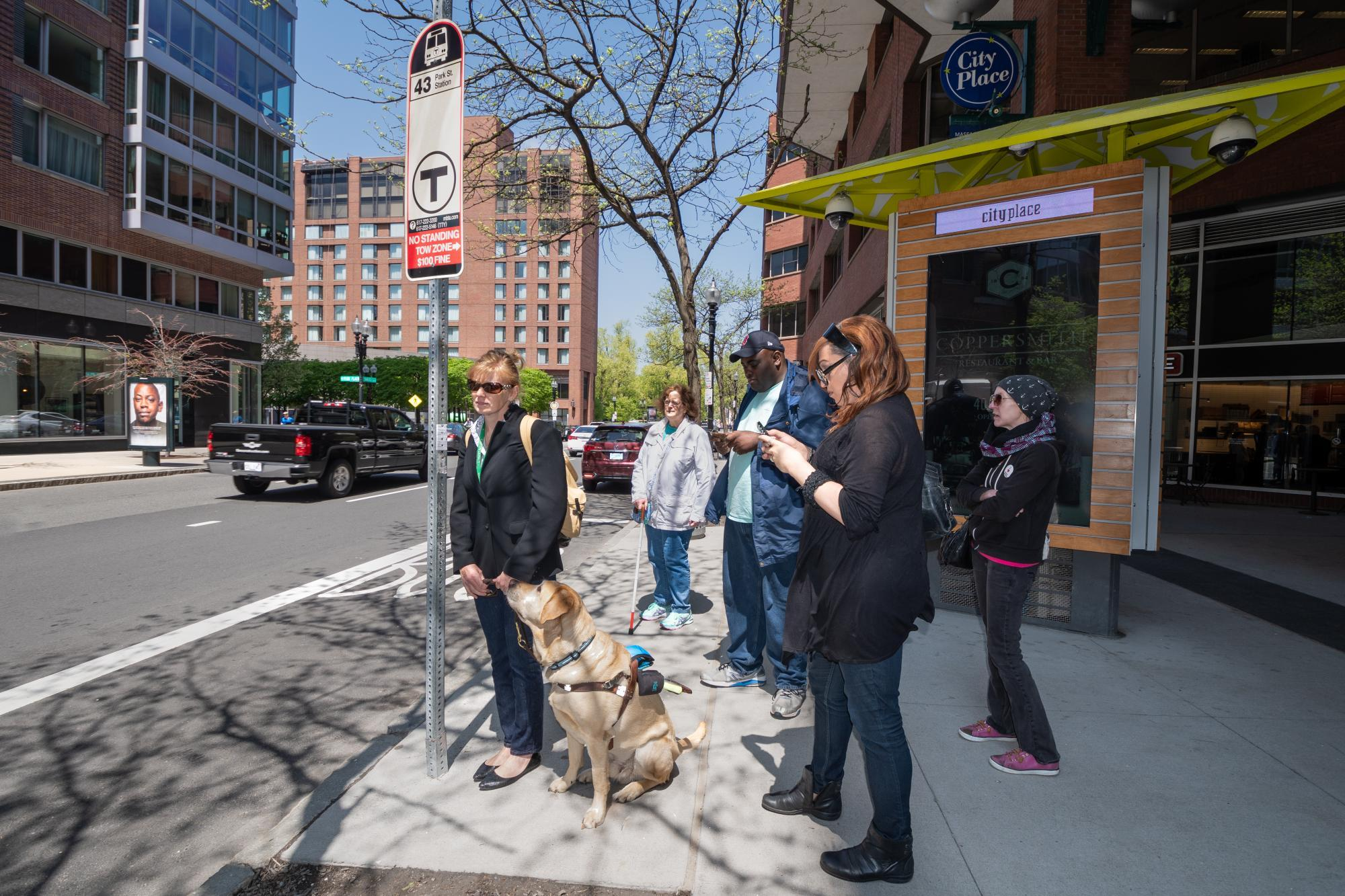 customers waiting at bus stop with guide dog