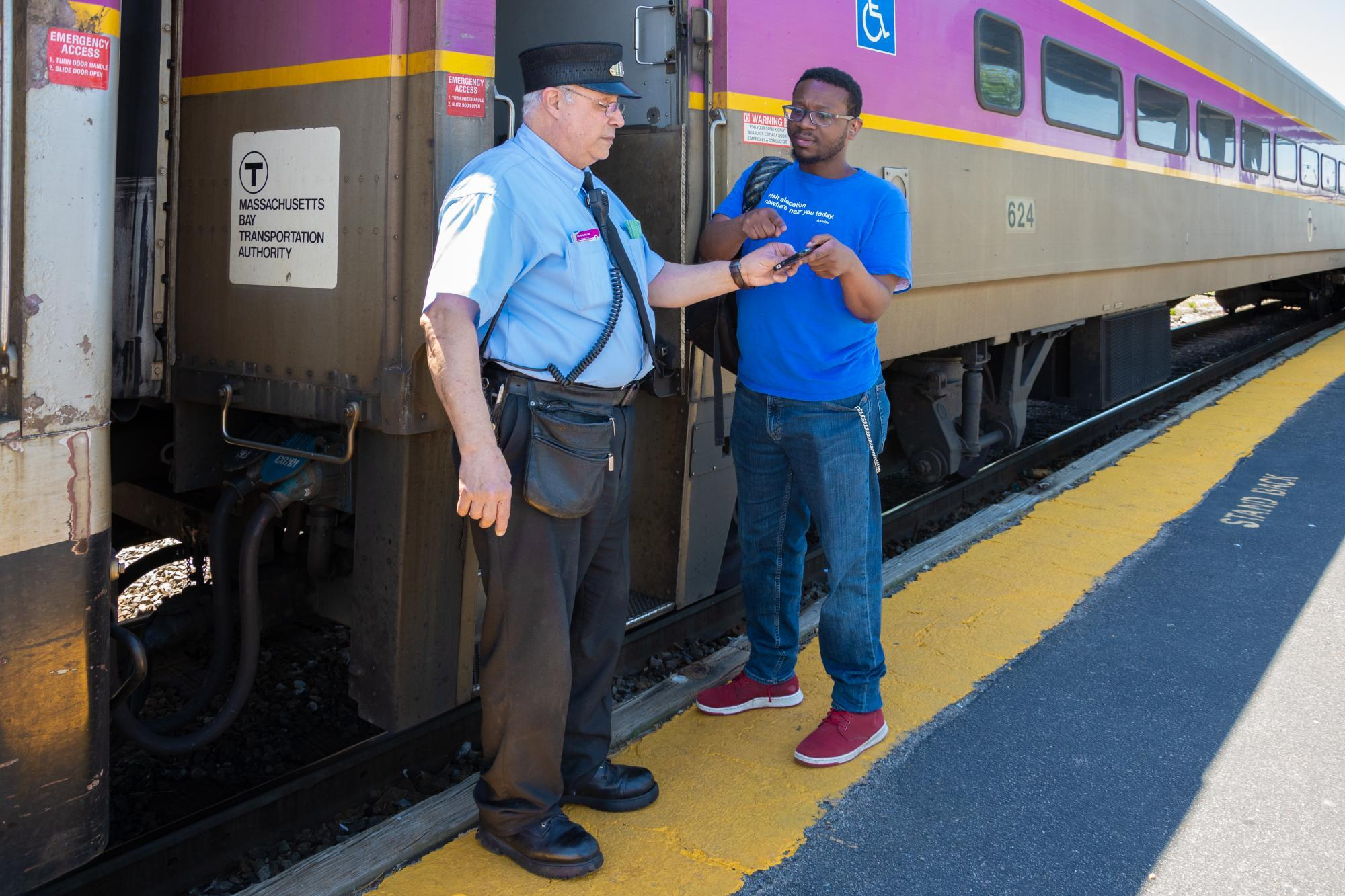 commuter rail conductor assisting customer