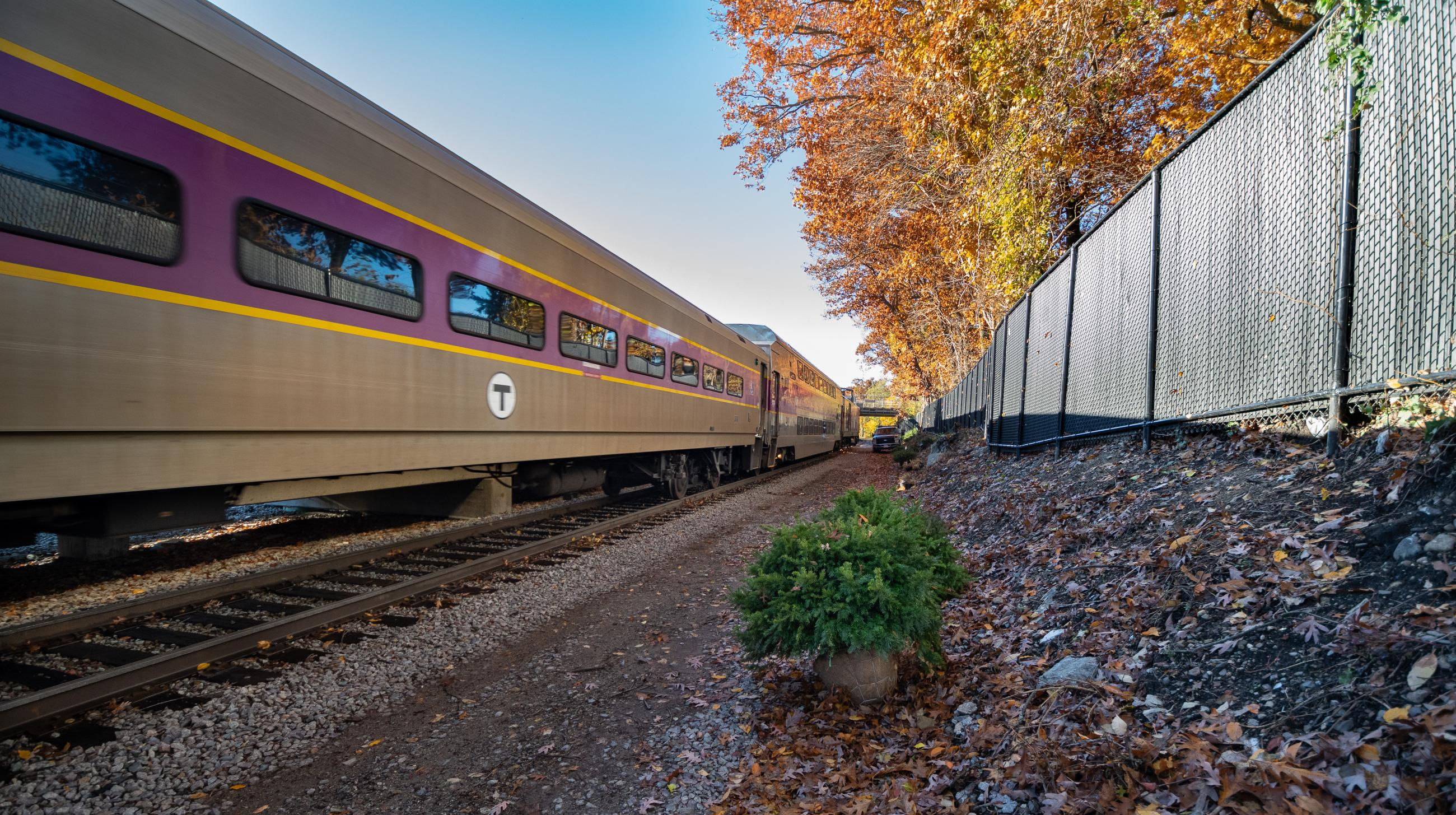 Commuter Rail Train Drives Through Blue Hill Avenue Station in Fall