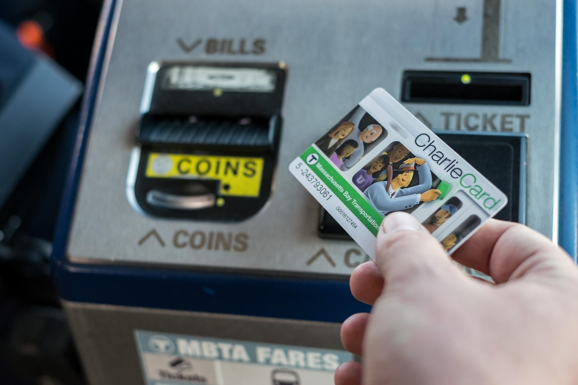 A rider taps his CharlieCard on a farebox while boarding the bus