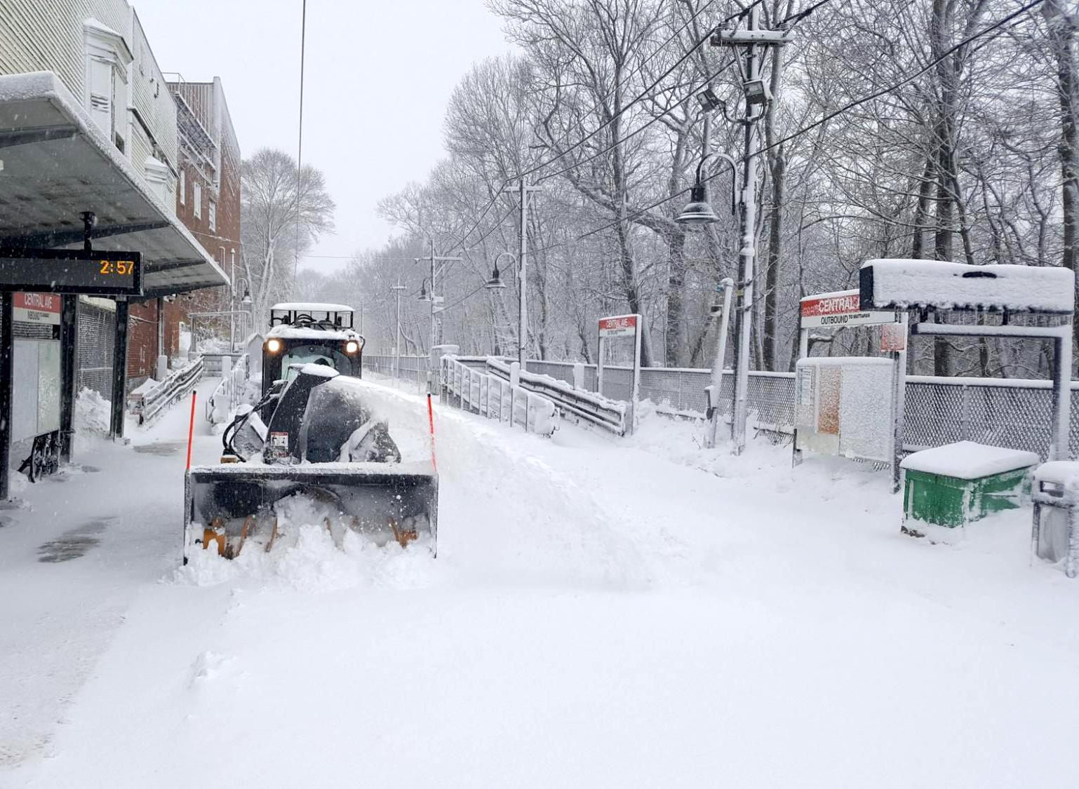 A plow clears snow from the tracks at Central Ave Station on the Mattapan Line