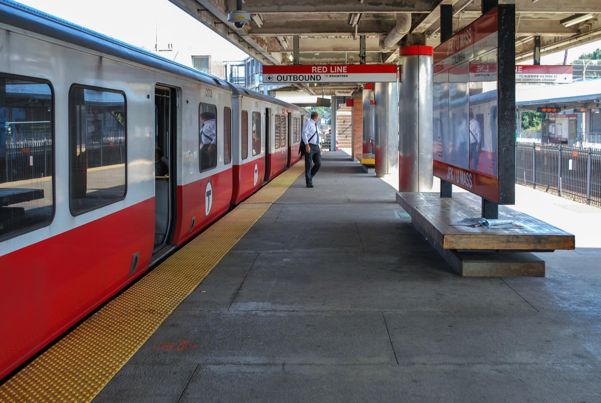 A man on the sunlit JFK/UMass platform, with a Red Line train pulled up