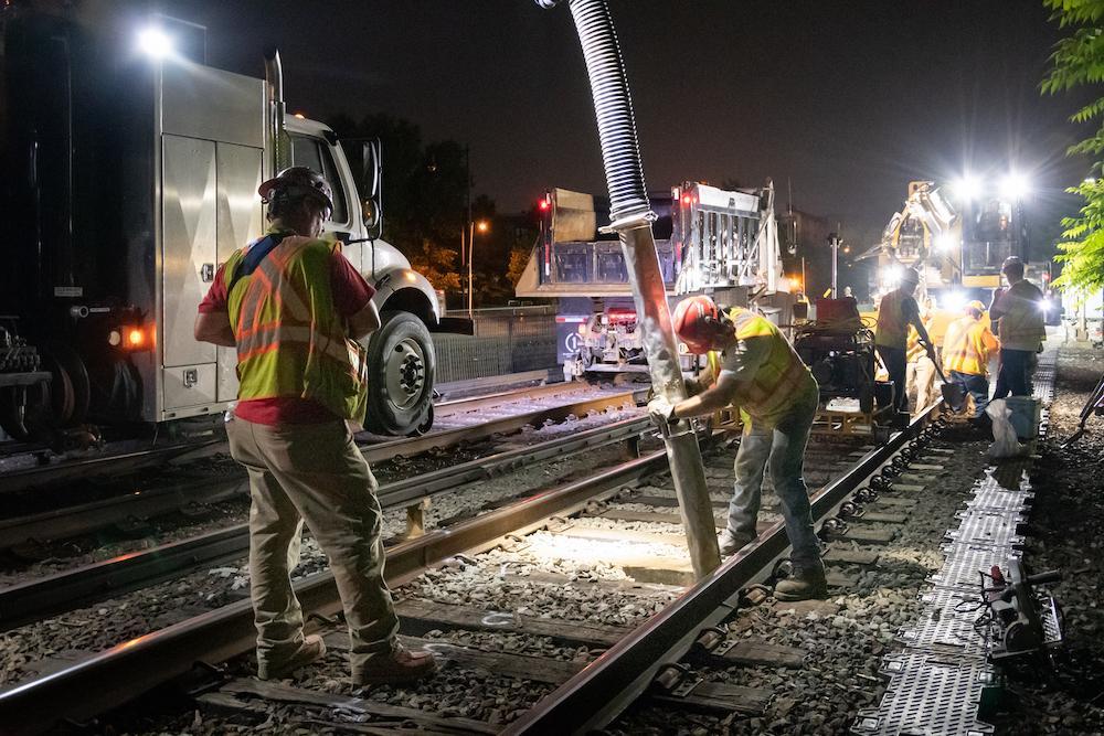 A crew member vacuums up ballast before replacing rail ties on the Orange Line in Medford.