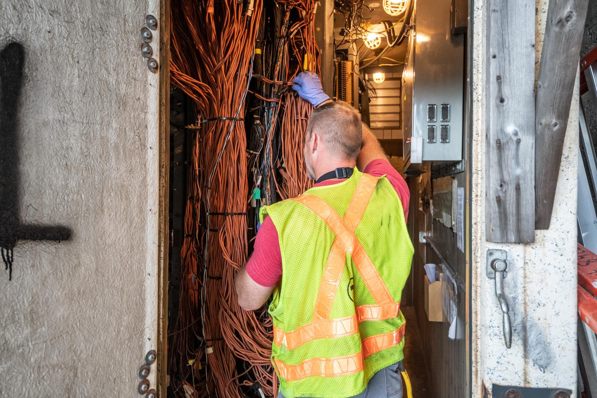 A worker in a neon vest handles wiring during signal repair at the JFK/UMass signals bungalow.