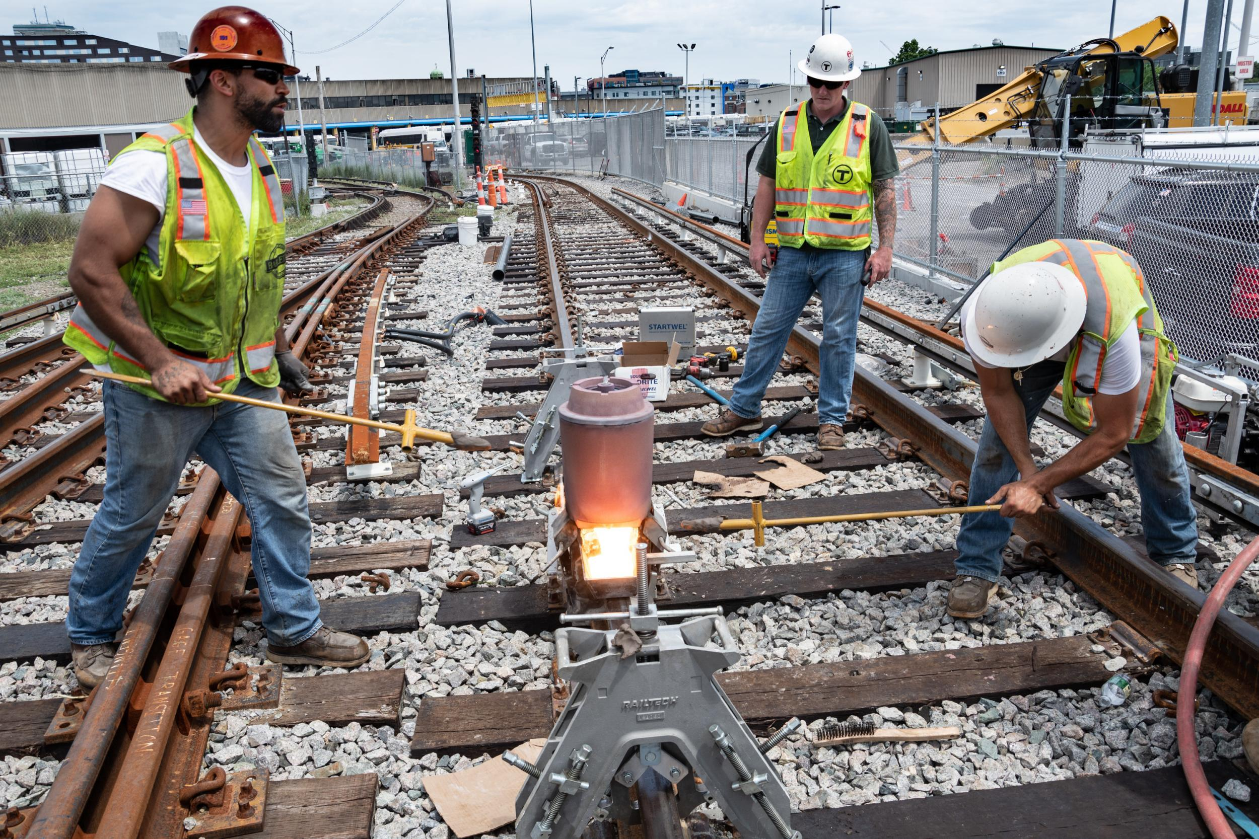 A crew along the Red Line test track in Cabot Yard uses exothermic welding to fuse separate pieces of rail together.