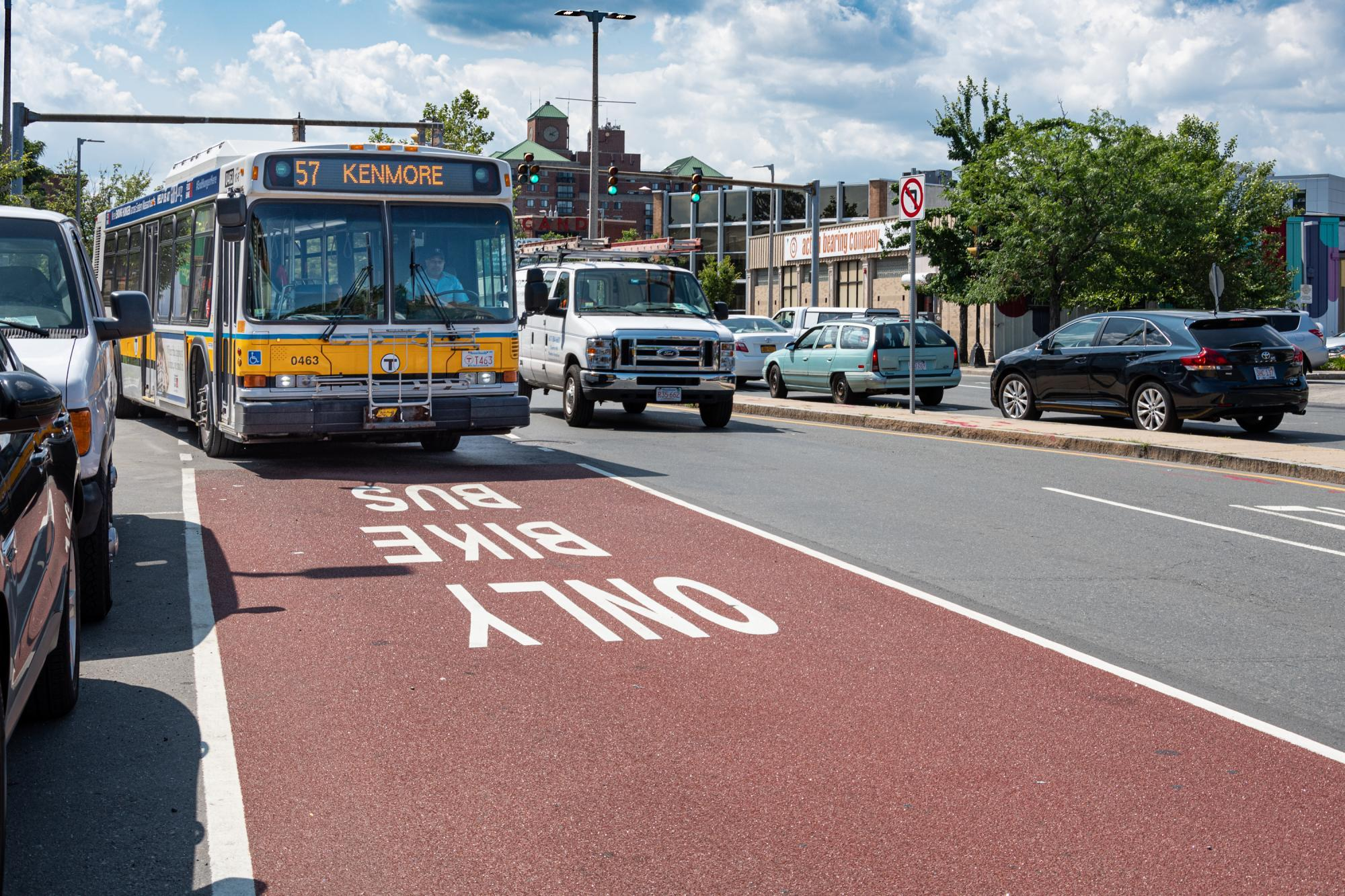 "A 57 bus travels in a dedicated bus lane on Brighton Ave in Allston, with ""Bus Bike Only"" prominently stenciled in the dark red lane."
