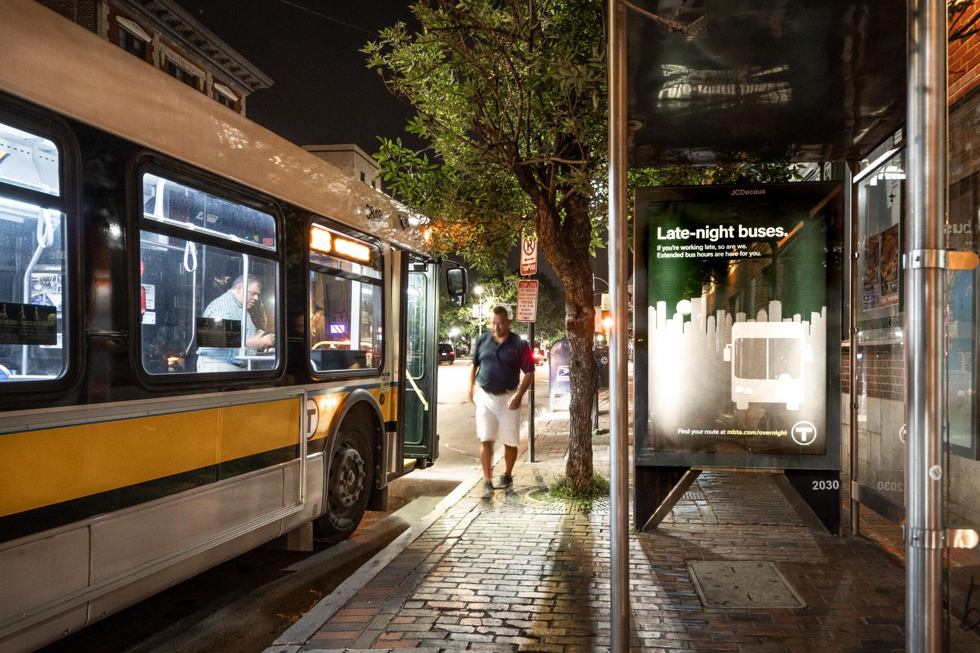 "A bus pulled up to a bus shelter late at night, with a rider walking away, and an ad for late night bus service on the shelter wall, which reads, ""Late-night buses. If you"