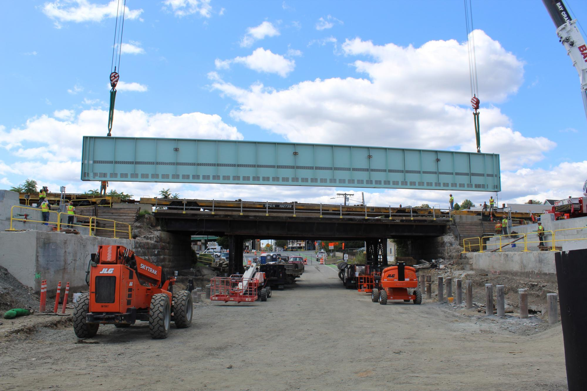 A crane lowers a large, green, steel girder beam into place on the Washington Street Bridge/Underpass in Somerville. They are the first steel bridge girders to be installed as part of GLX.