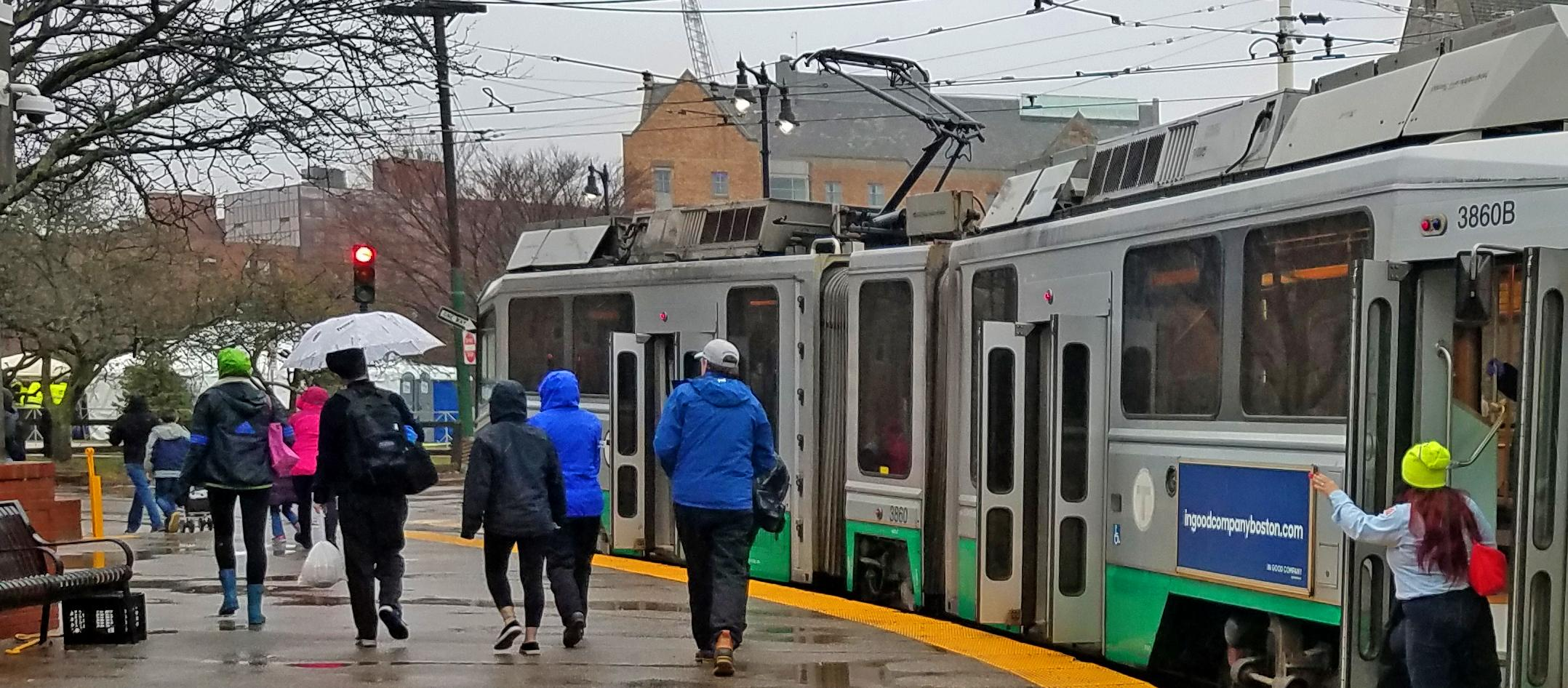 Riders near the Green Line during rainy weather at Boston Marathon 2018