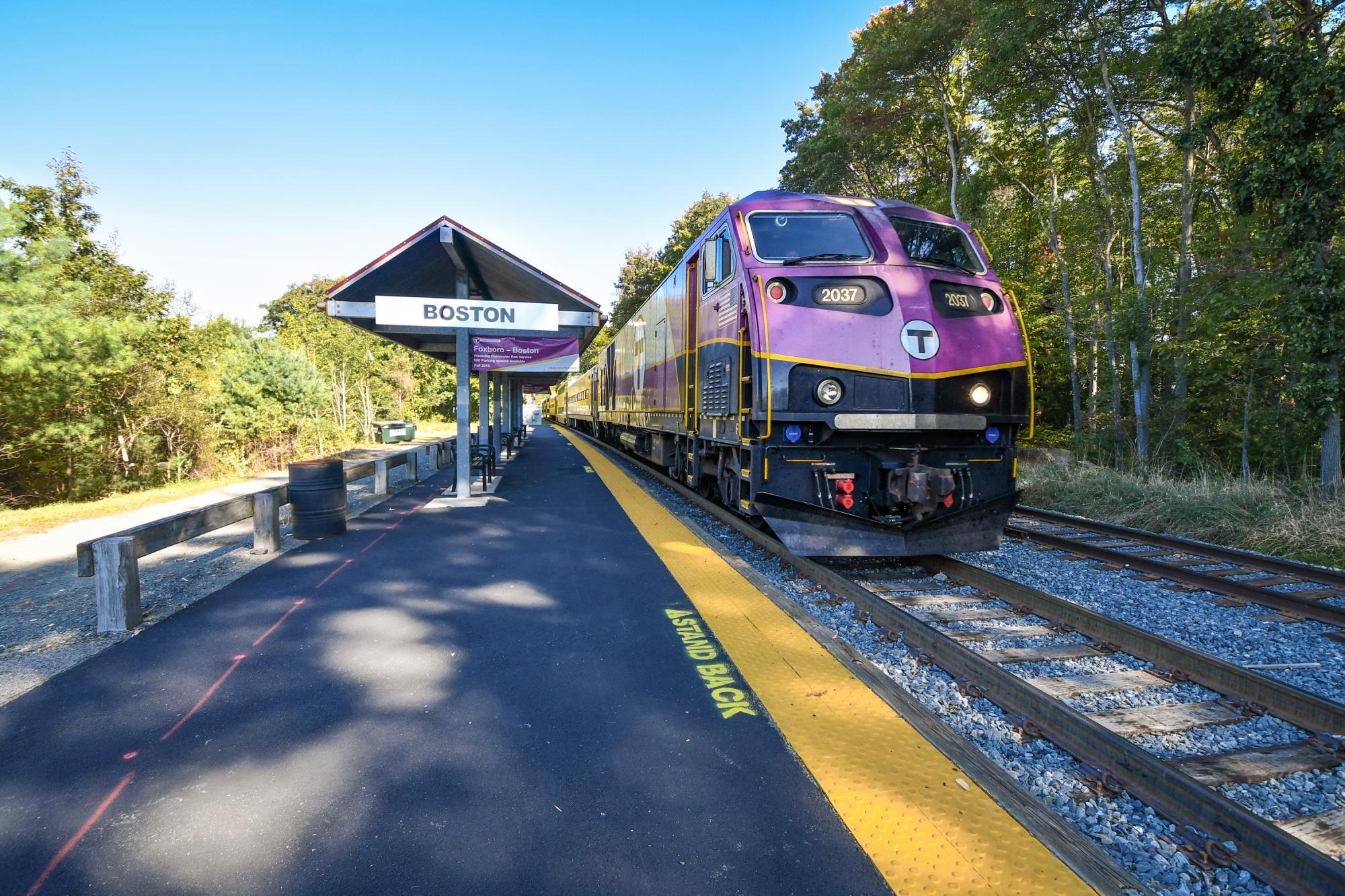 A Commuter Rail train pulls away from Foxboro Station, inbound for Boston. In the background is a sign adveristing the Foxboro - Boston weekday pilot.