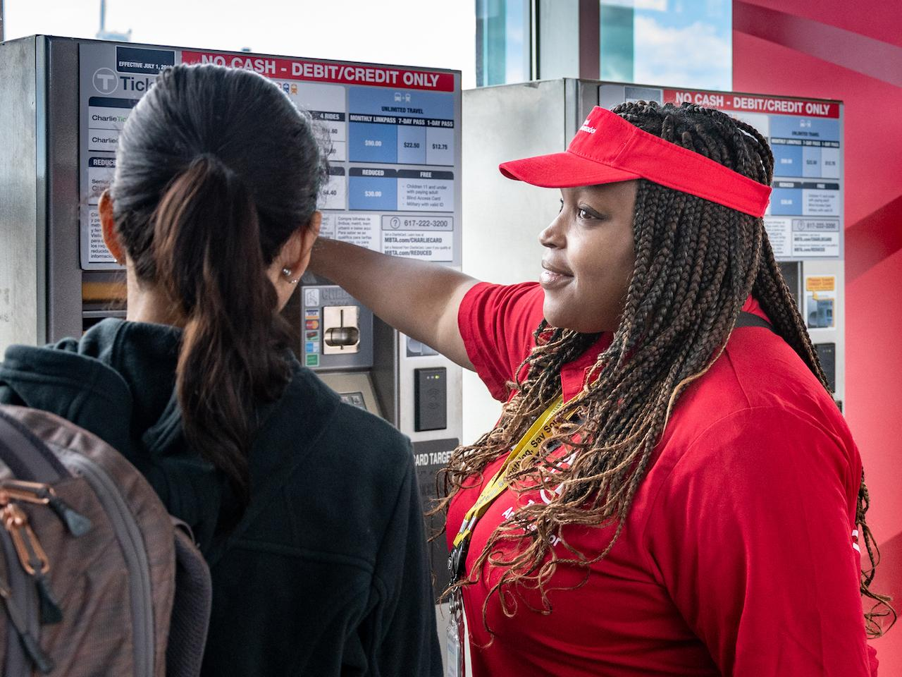A Transit Ambassadors helps a rider with at fare vending machine at Assembly Station.