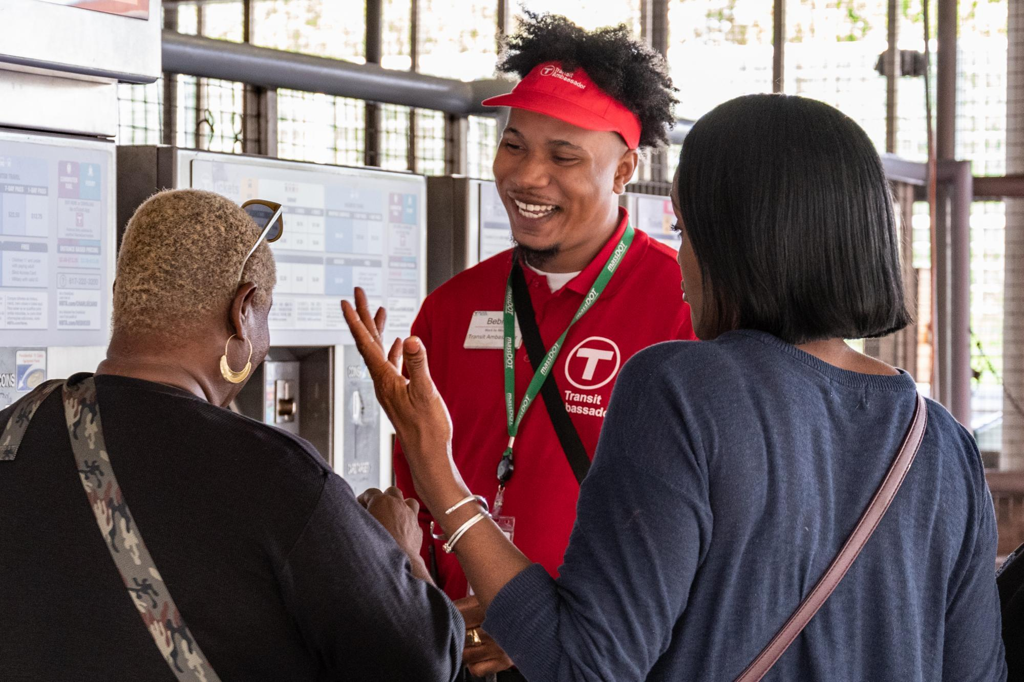 A smiling Transit Ambassador speaks with 2 riders near the fare vending machines at Ruggles Station.