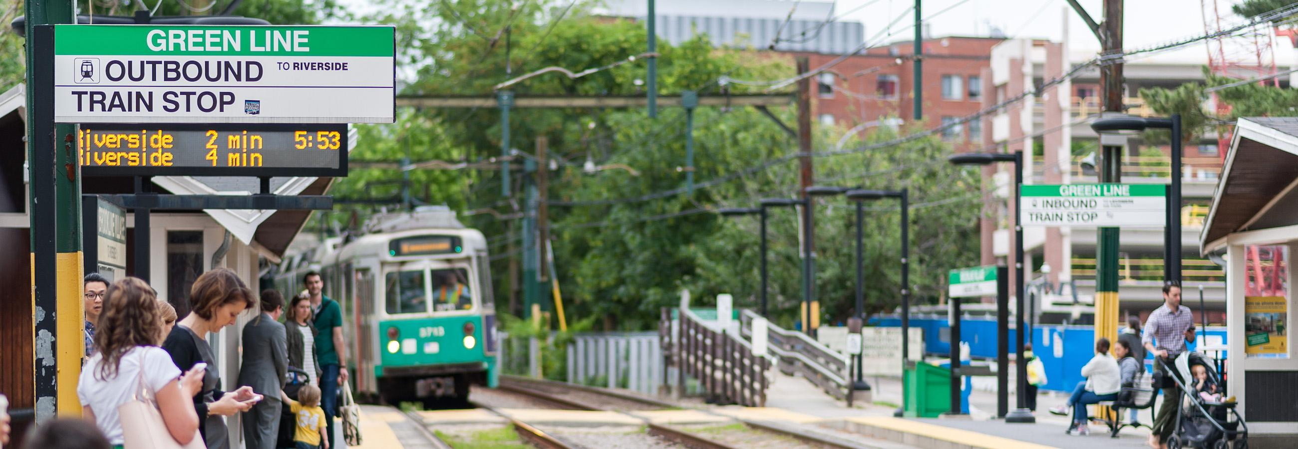 customers wait for arriving green line train at brookline village
