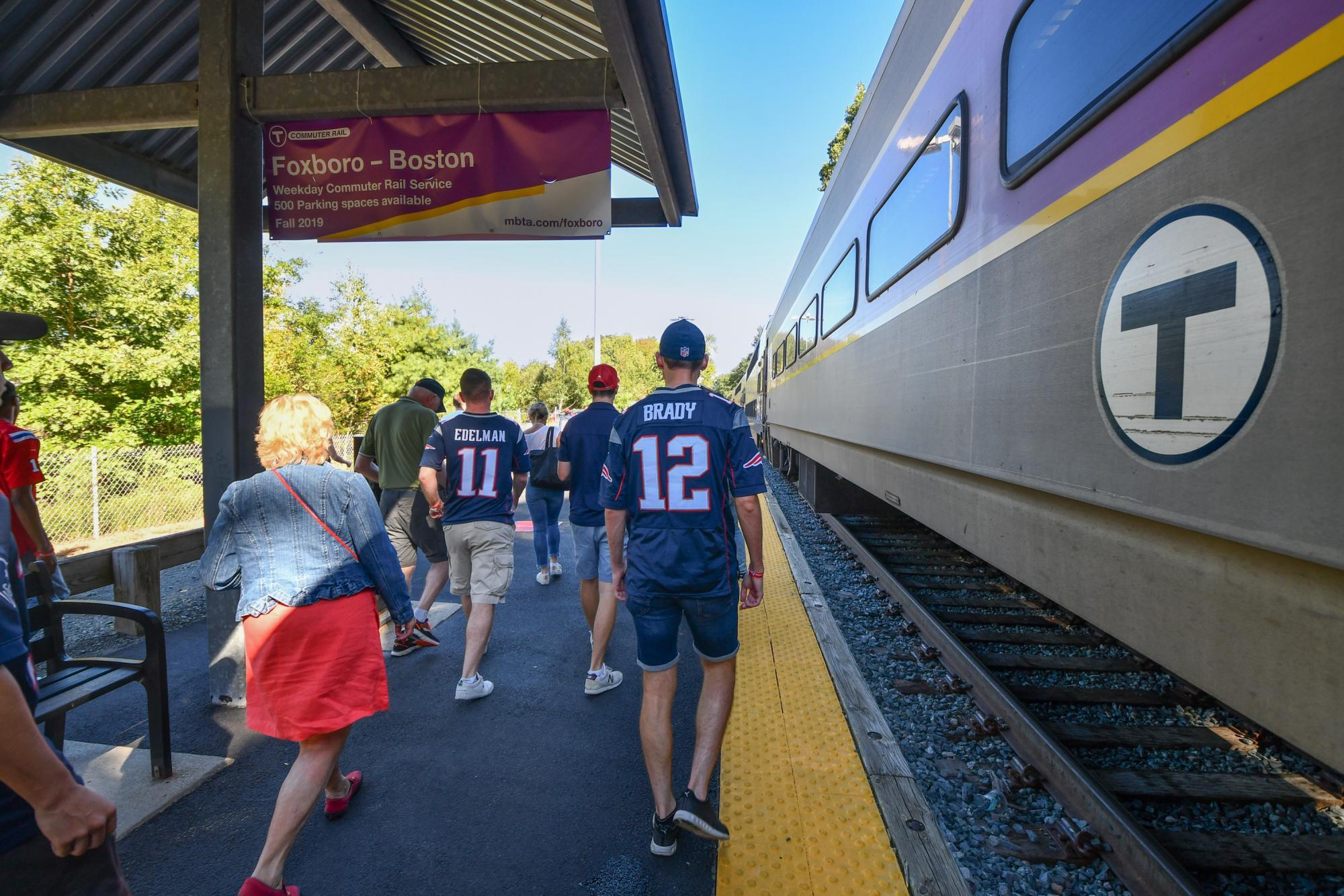 At Foxboro Station, riders with Patriots jerseys walk on the platform, passing by the Commuter Rail train.