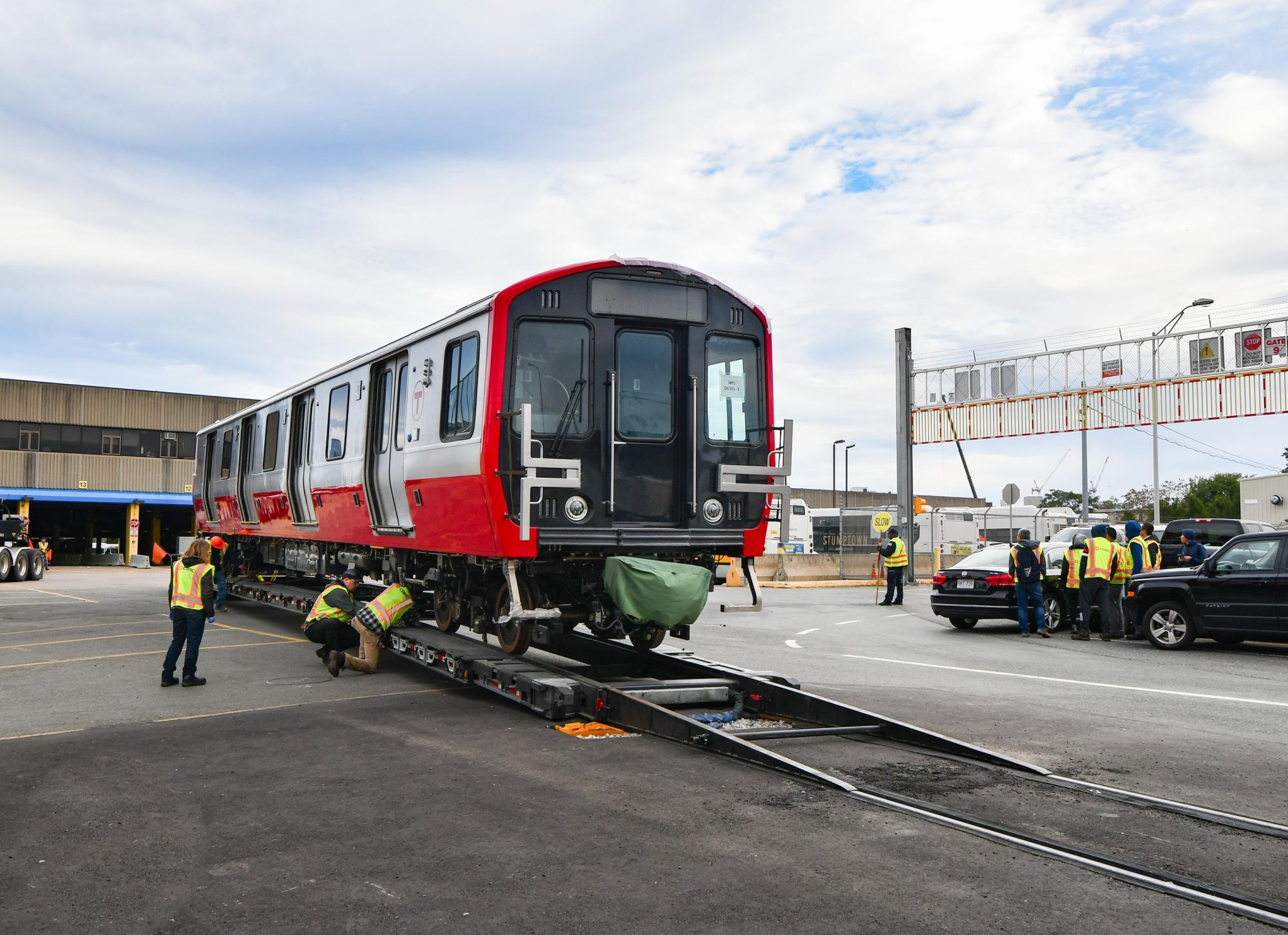 Red Line car being delievered to Cabot Yard, with MBTA workers helping to get it off the trailer.