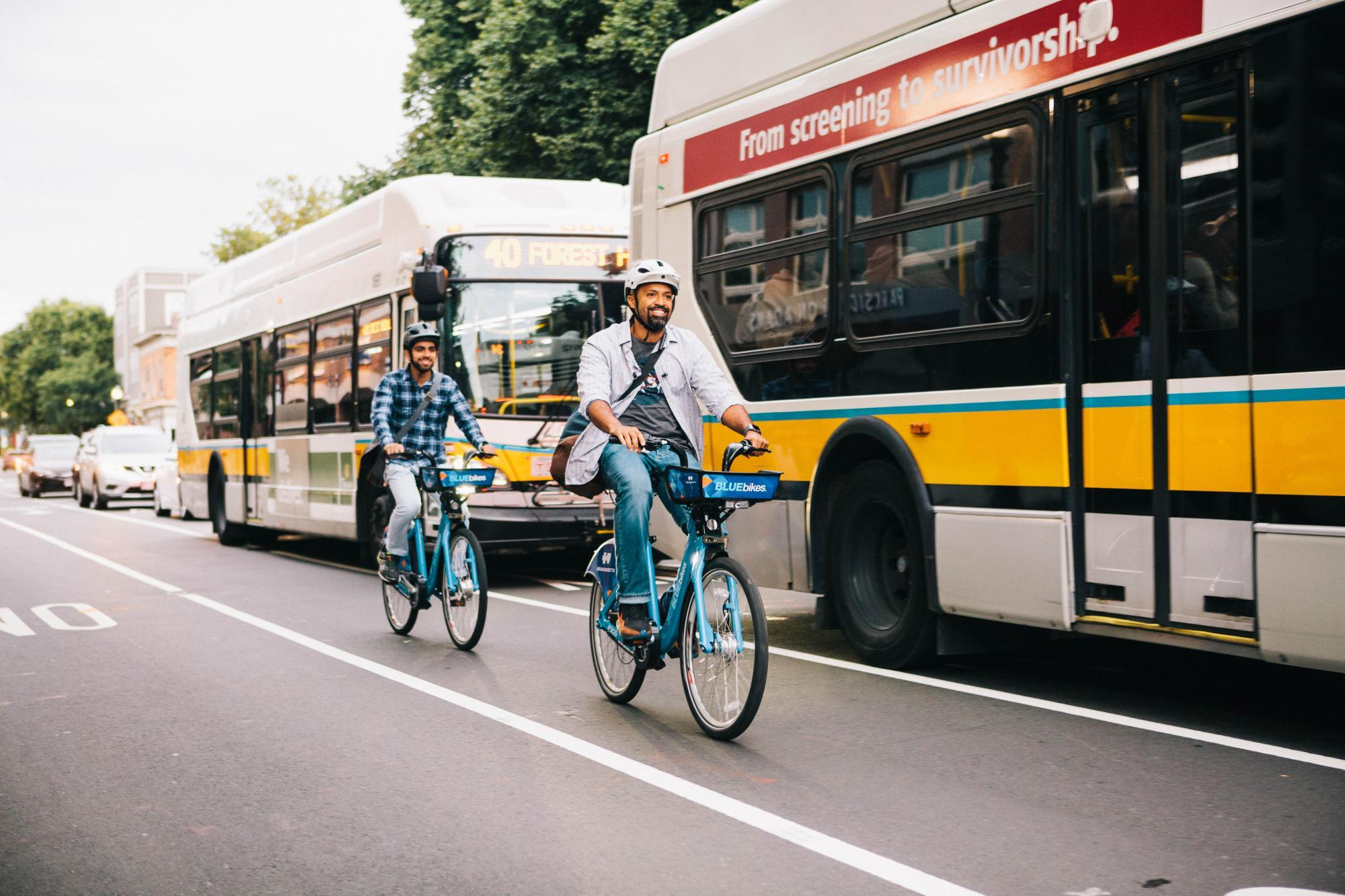 Two people ride Bluebikes in the bike lane, with 2 MBTA buses passing by them in the traffic lane. Photo courtesy of Bluebikes.