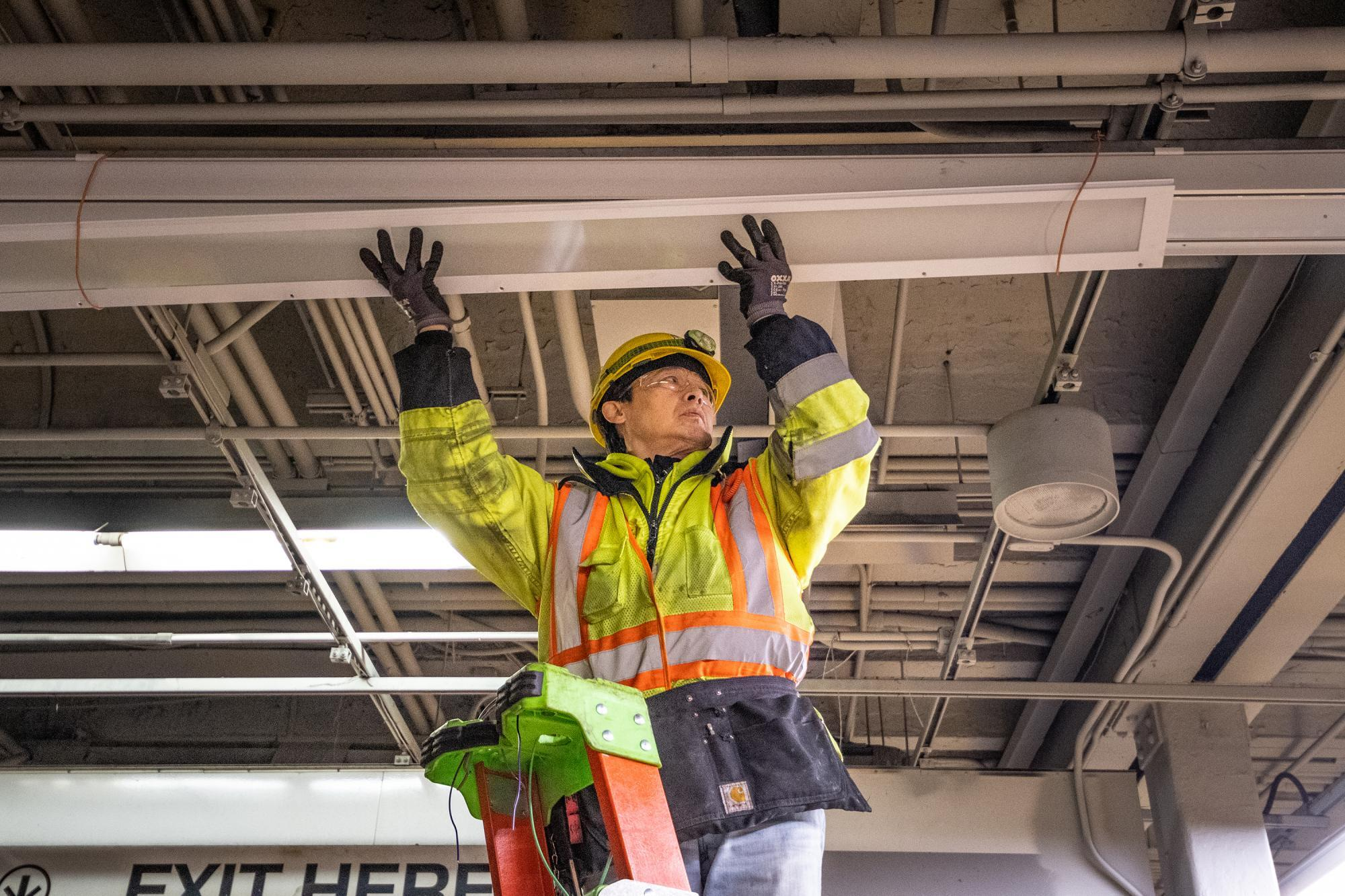 A crewman installs new lights above the Green Line at Park Street