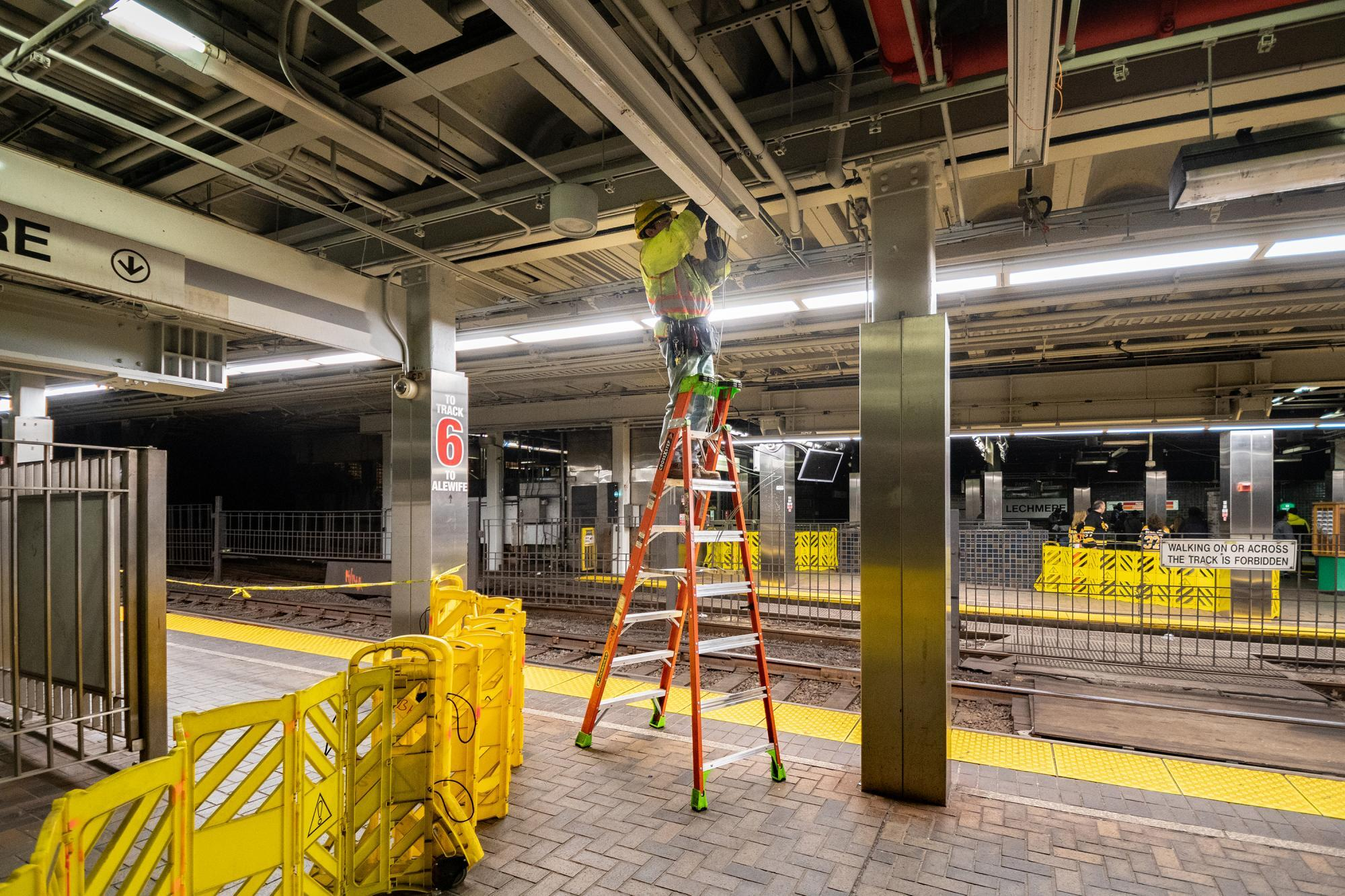 A crewman on a ladder installs new lights above the Green Line at Park Street