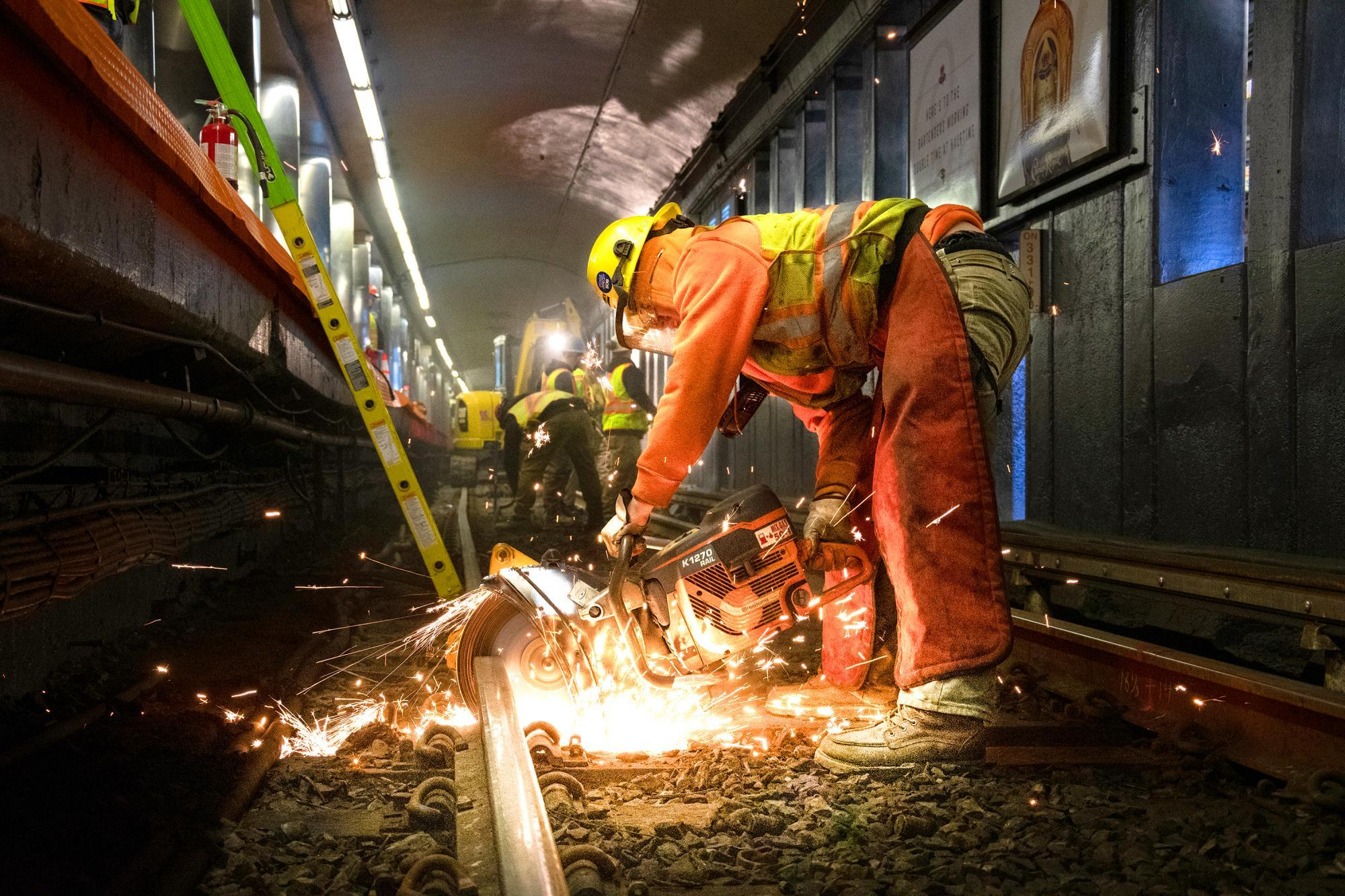 A crew member cuts track at Haymarket as part of rail replacement during the first Orange Line weekend shutdown of 2020